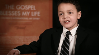 A young boy in a suit is interviewed by someone off camera
