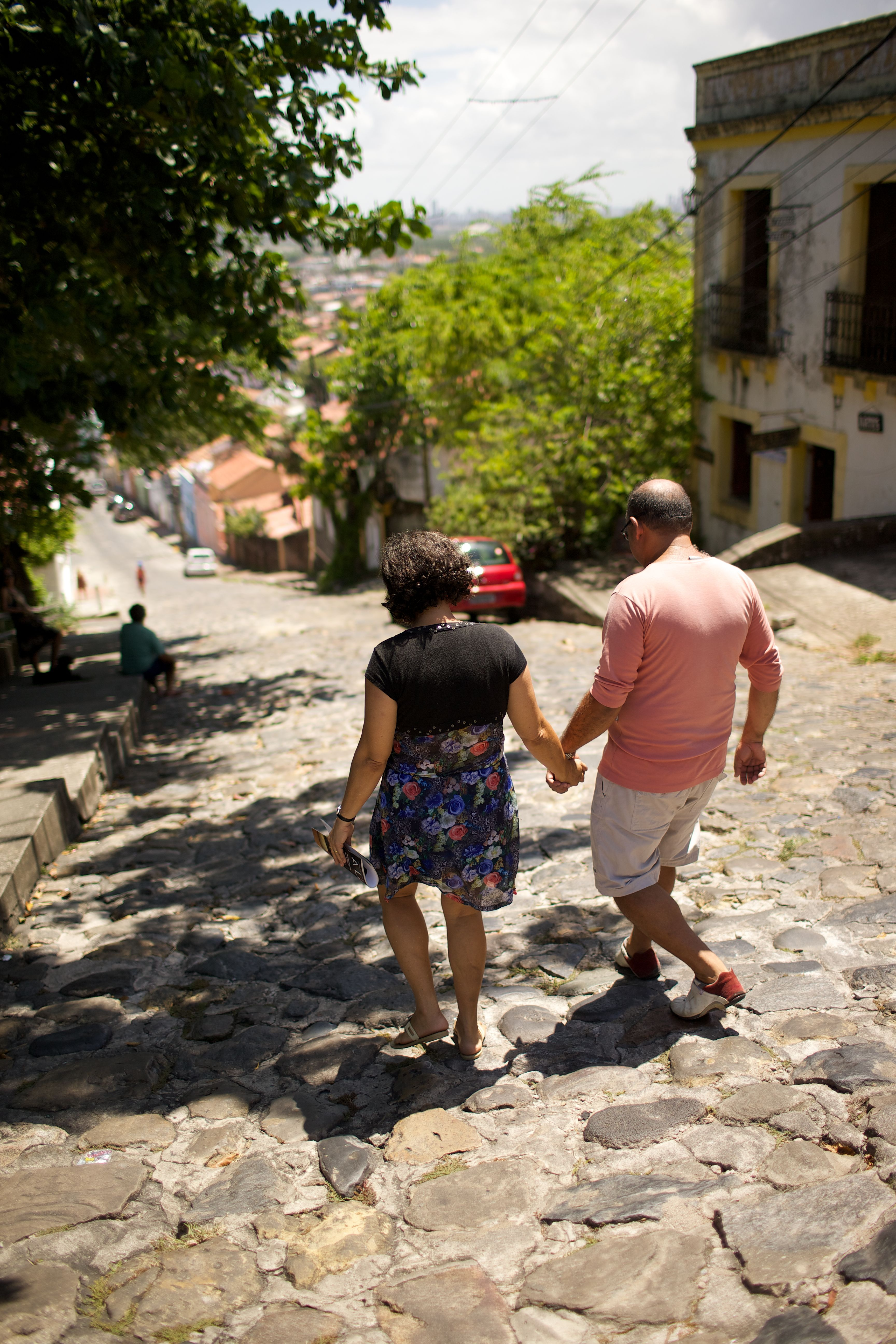 A couple holding hands and walking down a stone street in Brazil.