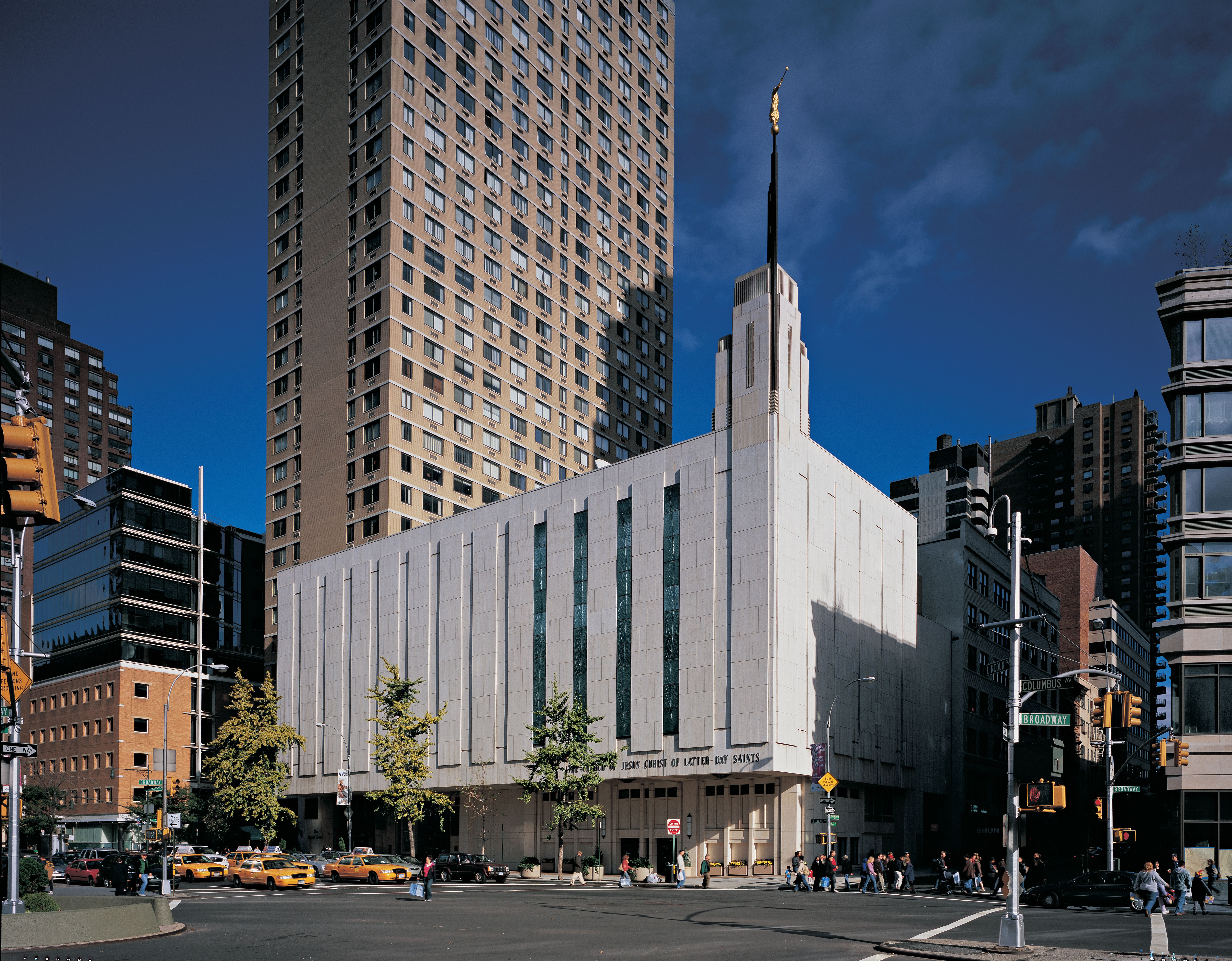 The Manhattan New York Temple against a dark sky, including the entrance and scenery.