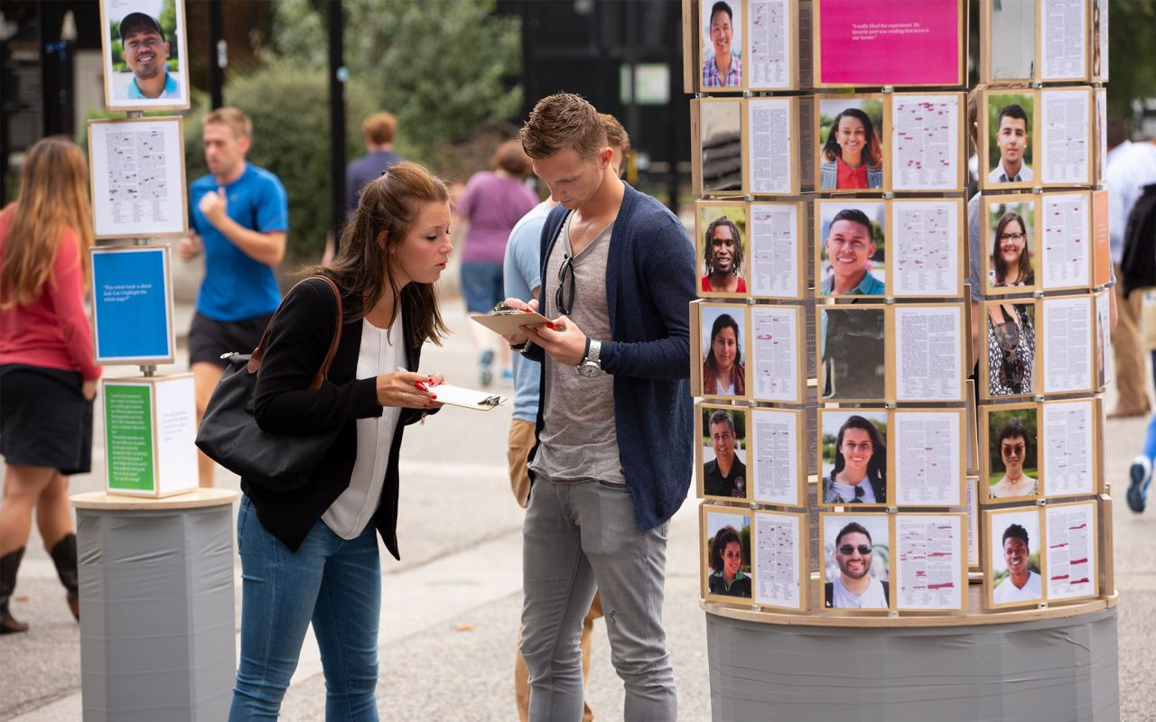 A man and woman mark Book of Mormon passages on clip boards learning about Jesus Christ