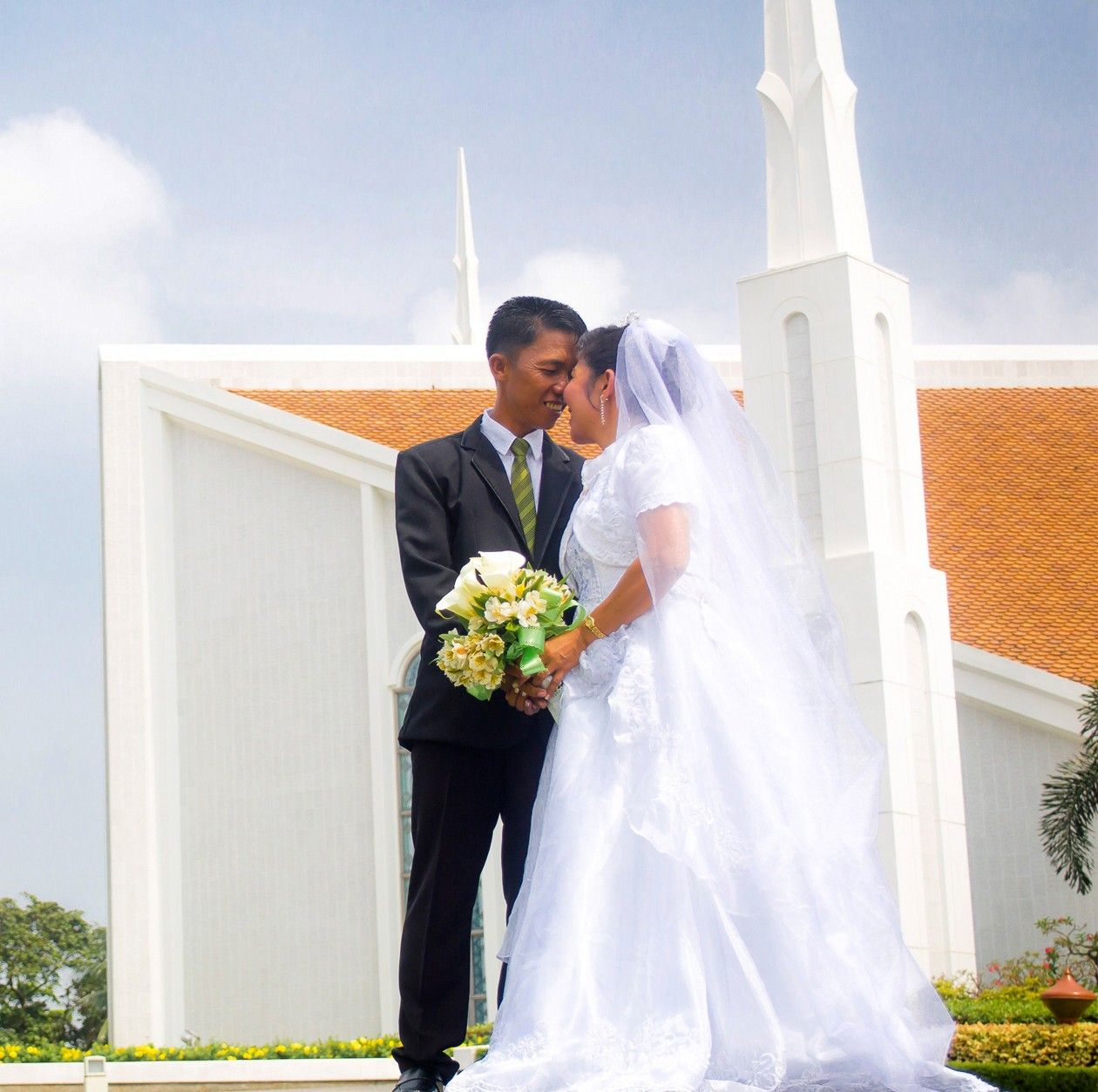 A bride and groom in front of the Manila Philippines Temple.