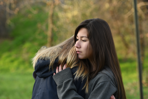 Young woman comforting another young woman