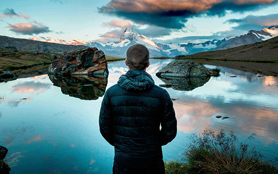 A man looks at a mountain lake seeing the hand of God in nature