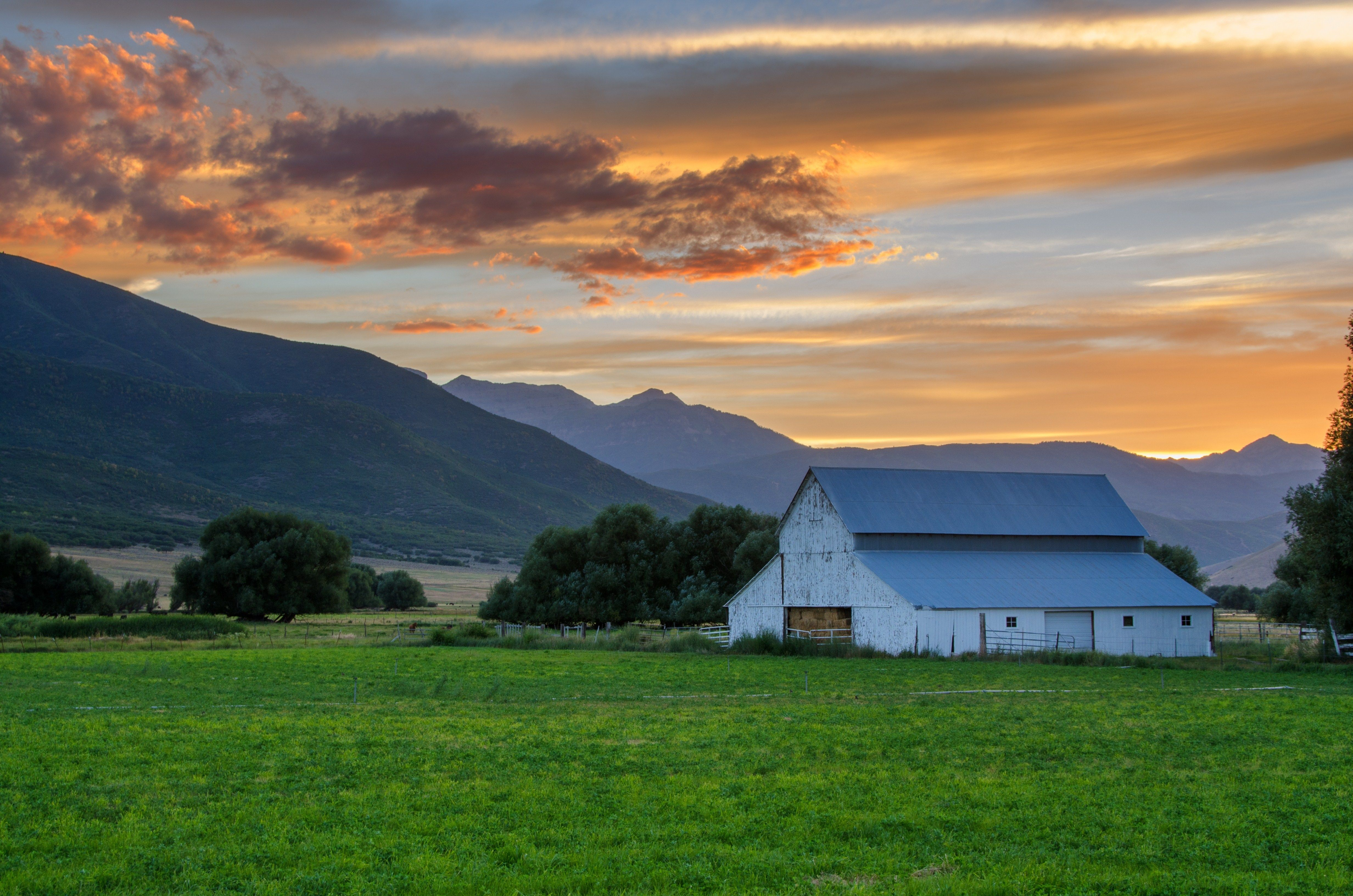 A sunset over farmland and a barn.