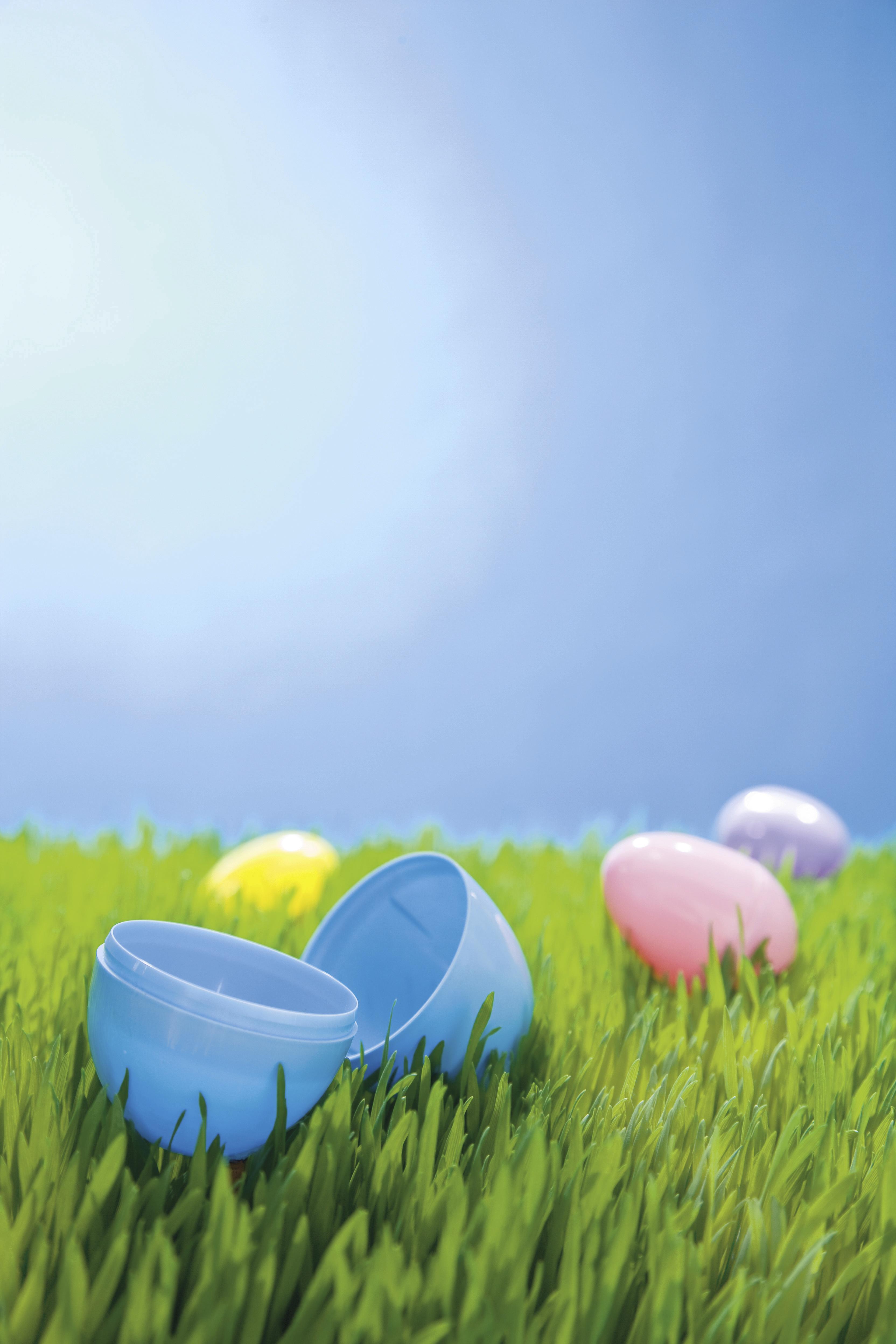 Several plastic Easter eggs lying in green grass.