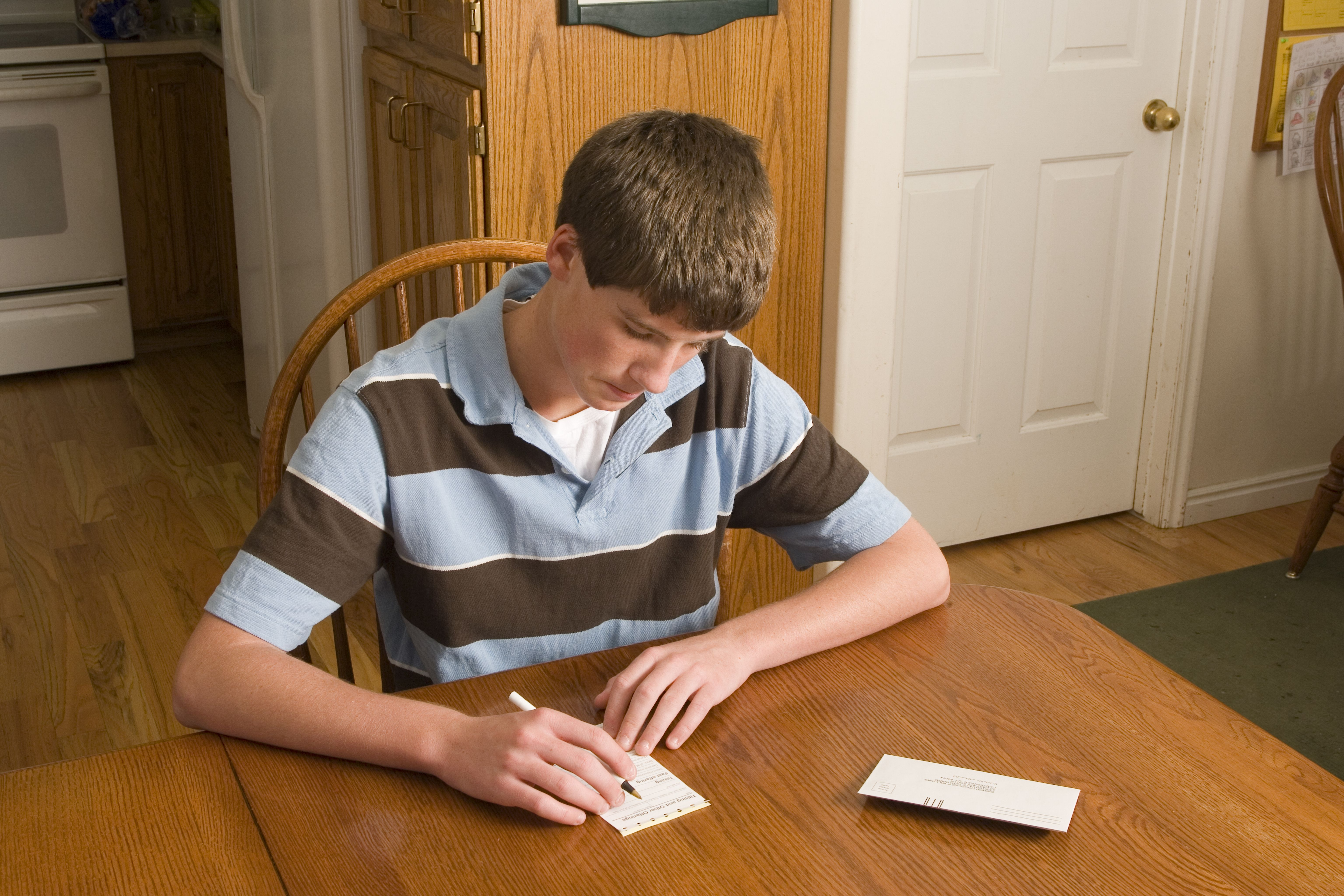 A young man fills out a tithing slip at the kitchen table.