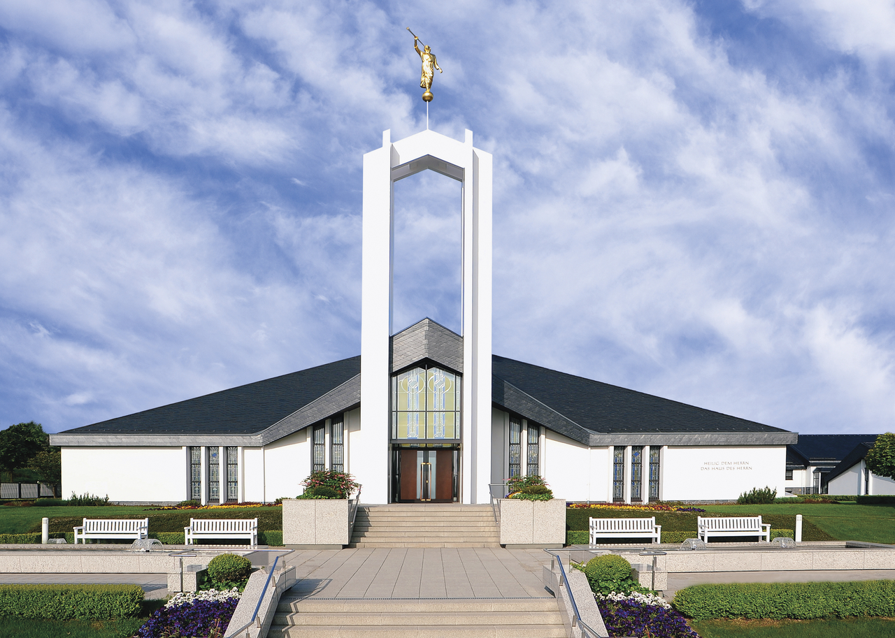 A view of the front of the Freiberg Germany Temple, with a bright blue sky and thin white clouds above the spire.