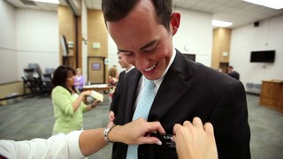 A young missionary has his tag pinned on by his mother's hands