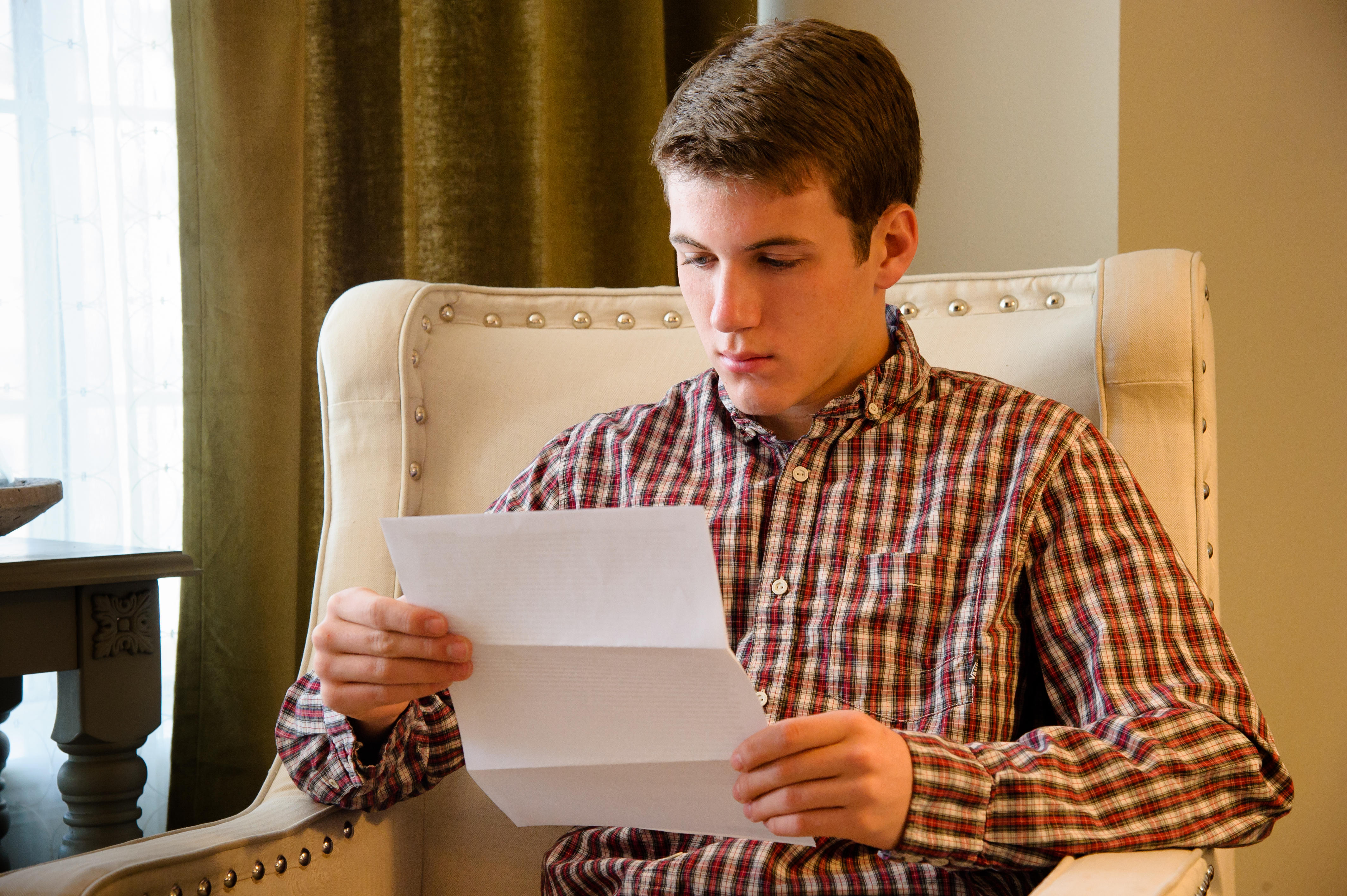 young man reading paper