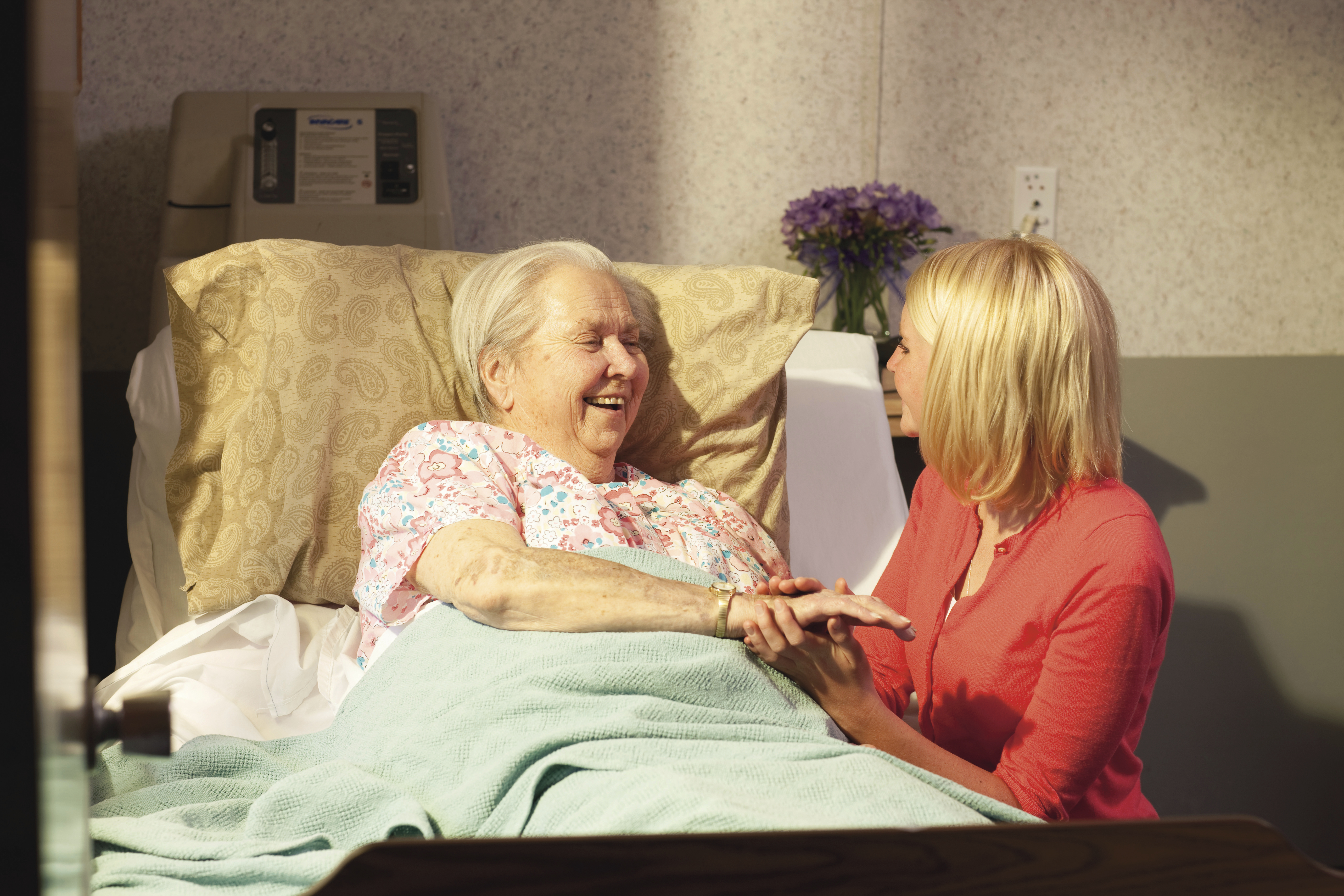 A young woman visits an elderly woman in the hospital.