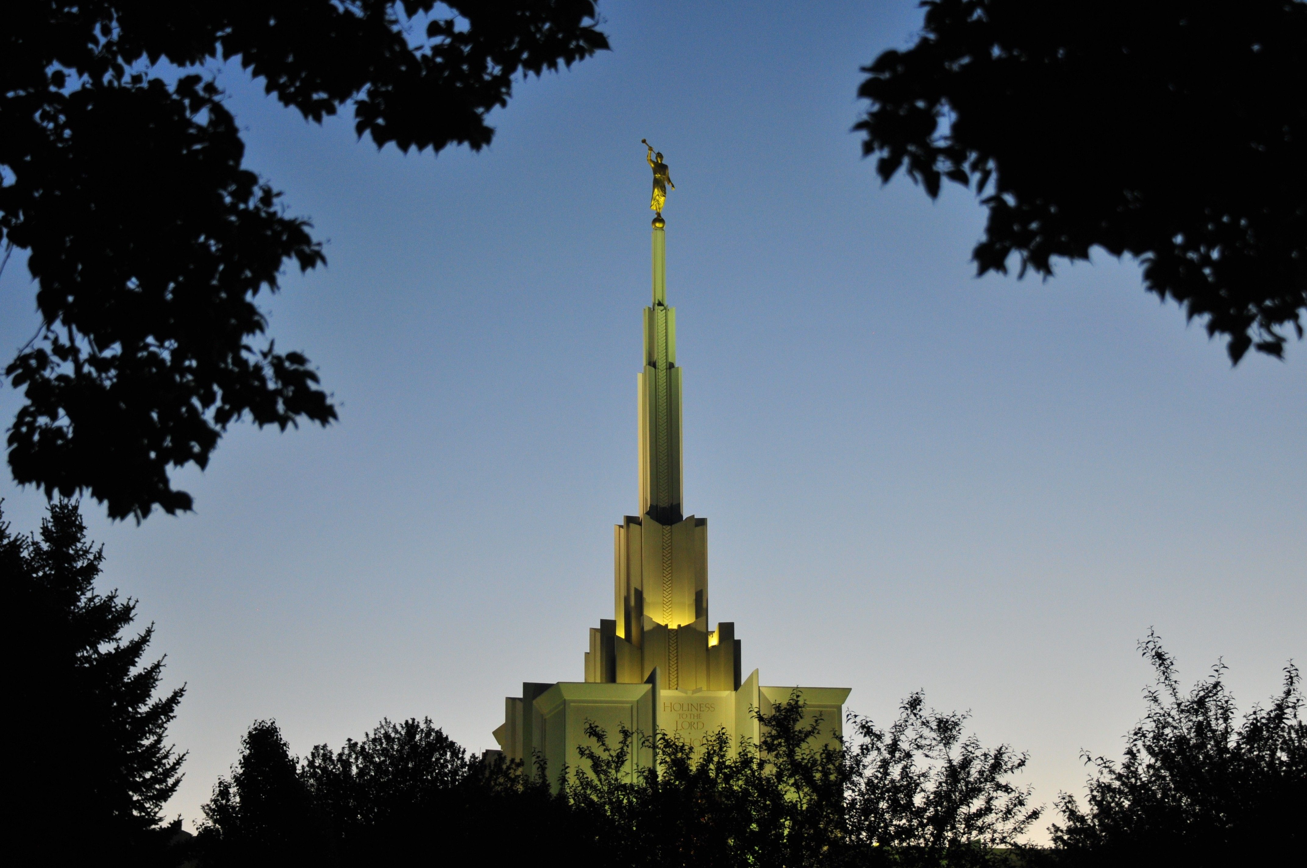 The spire of the Denver Colorado Temple is lit up at night.