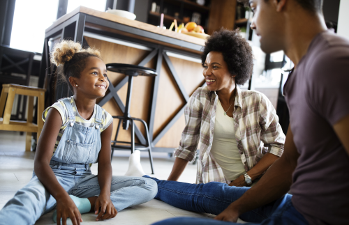 Black family sitting on the floor spending time together