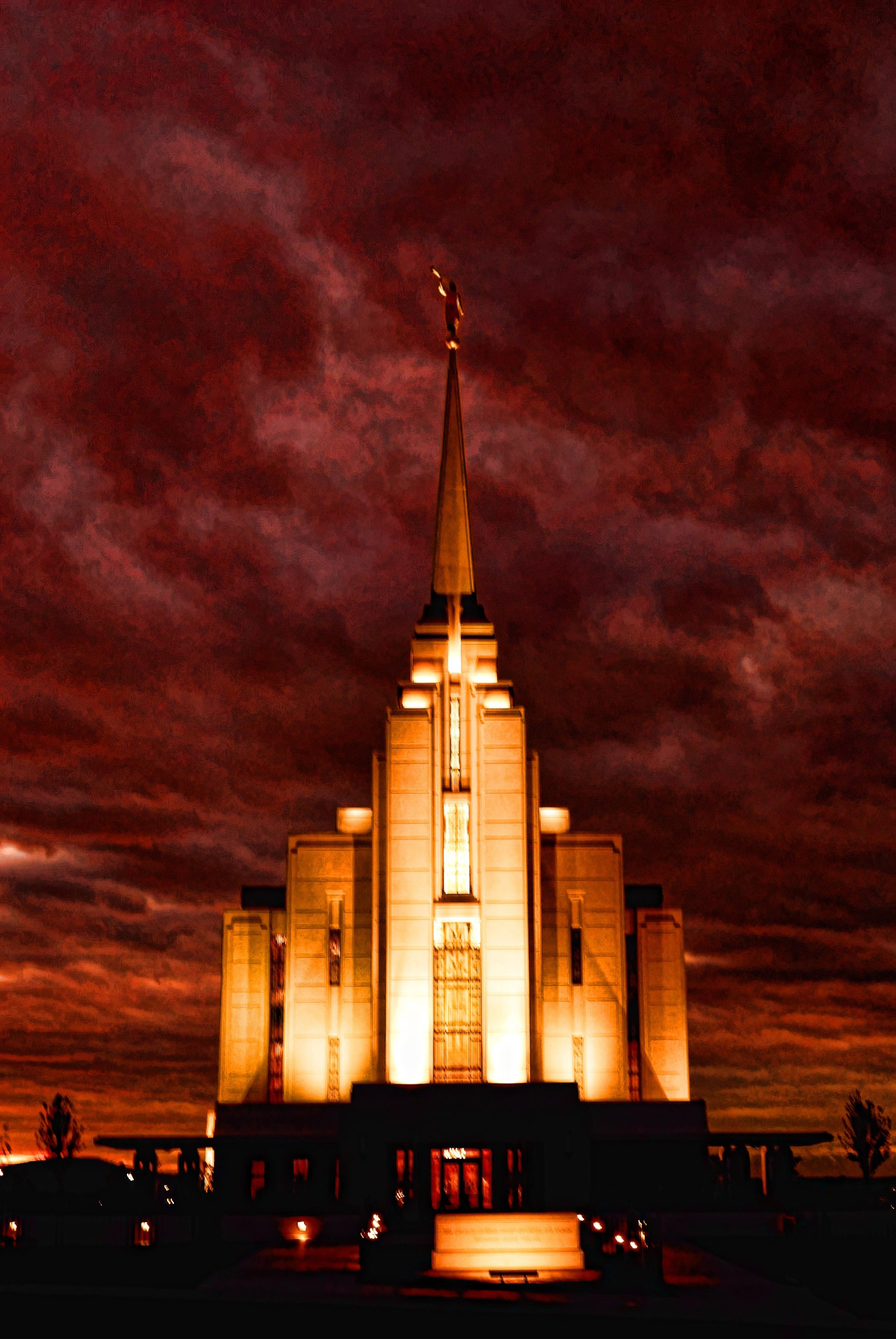 The Rexburg Idaho Temple in the evening during a storm, including the name sign.