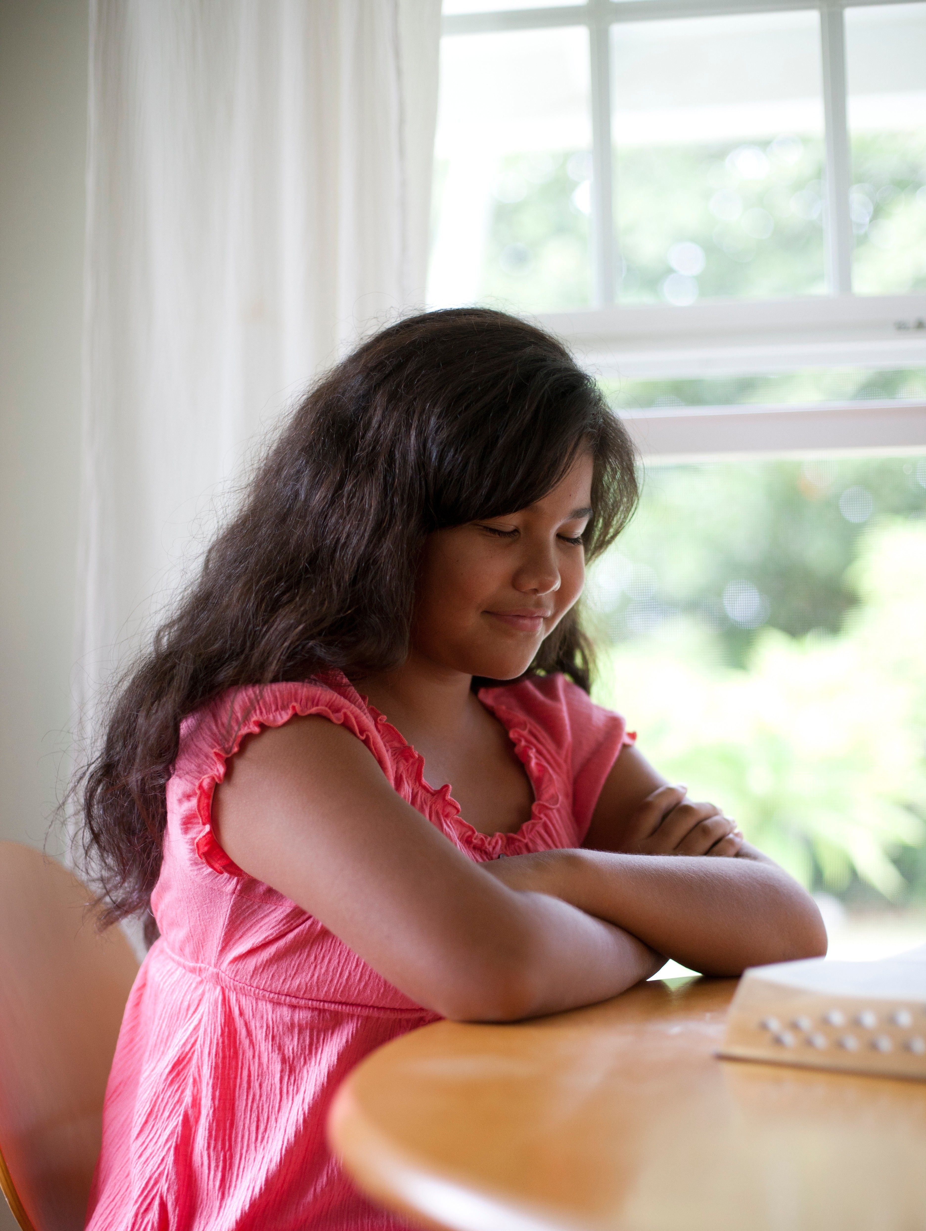 A young girl studies her scriptures at the table and prays.