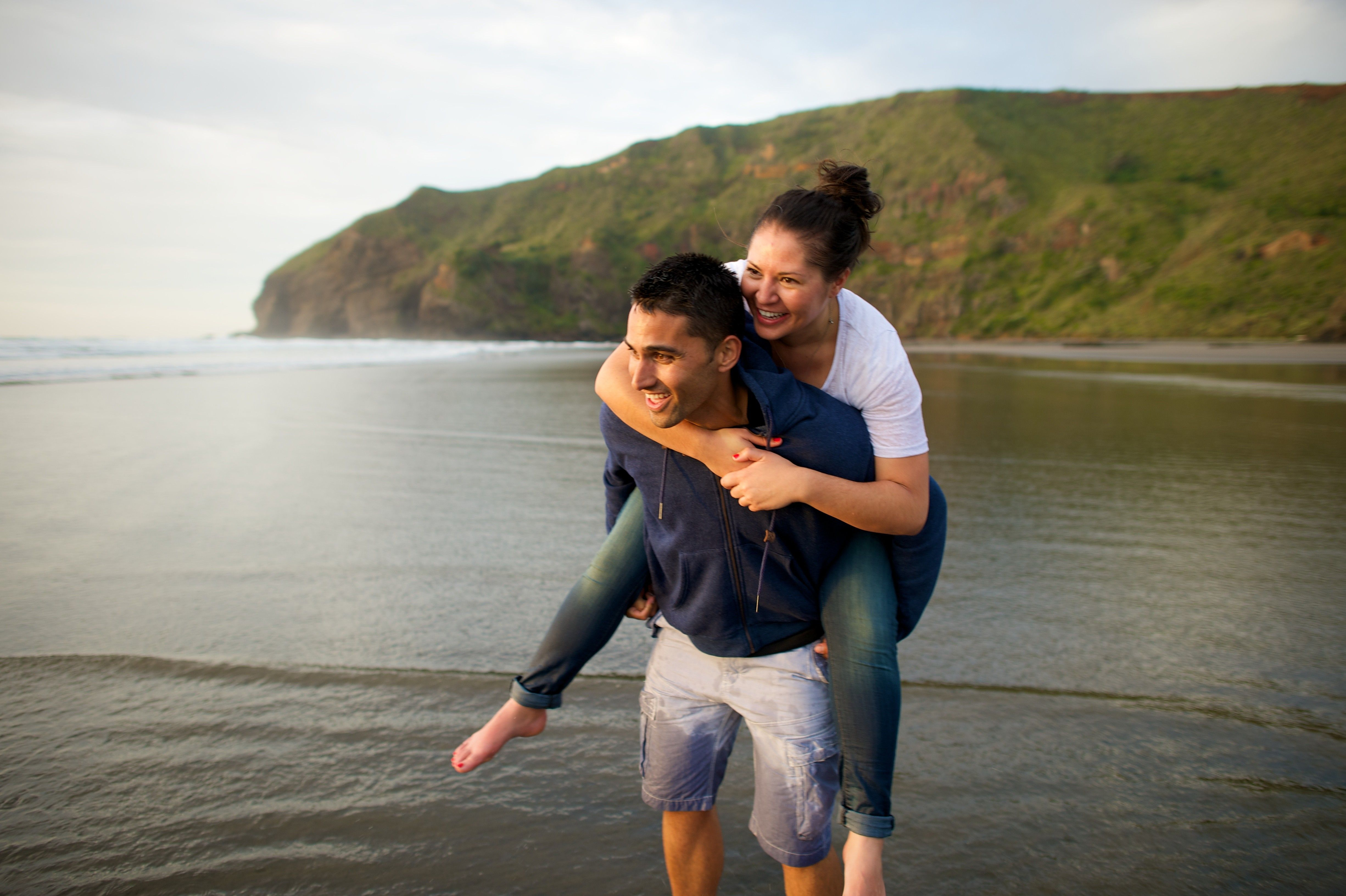 A young man carrying a young woman on his back at a beach in New Zealand.