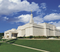 A front and side view of the Mérida Mexico Temple, with green grass and a blue sky with clouds.