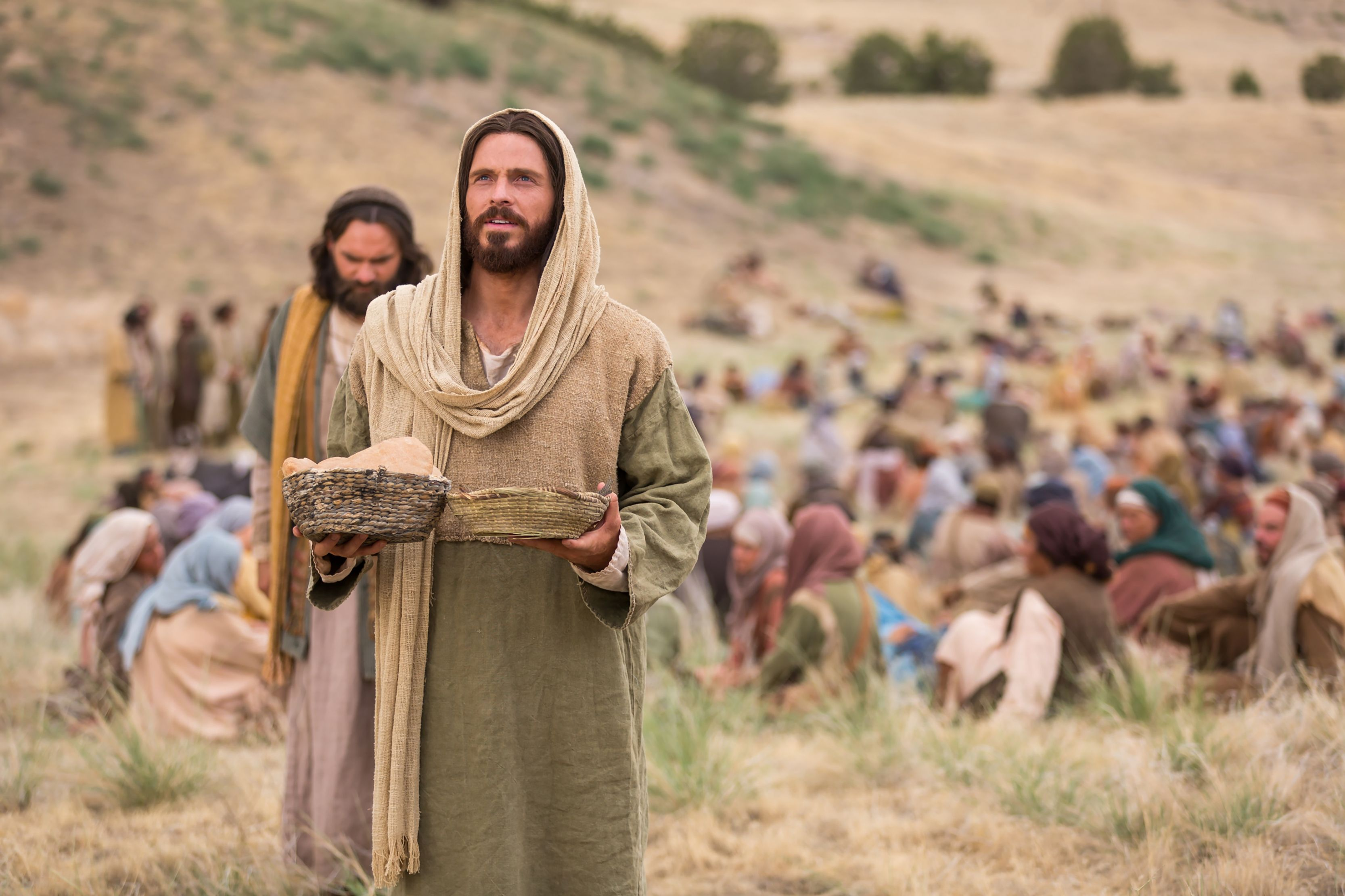 Jesus blesses the bread and fish to feed the people gathered to hear His teachings.