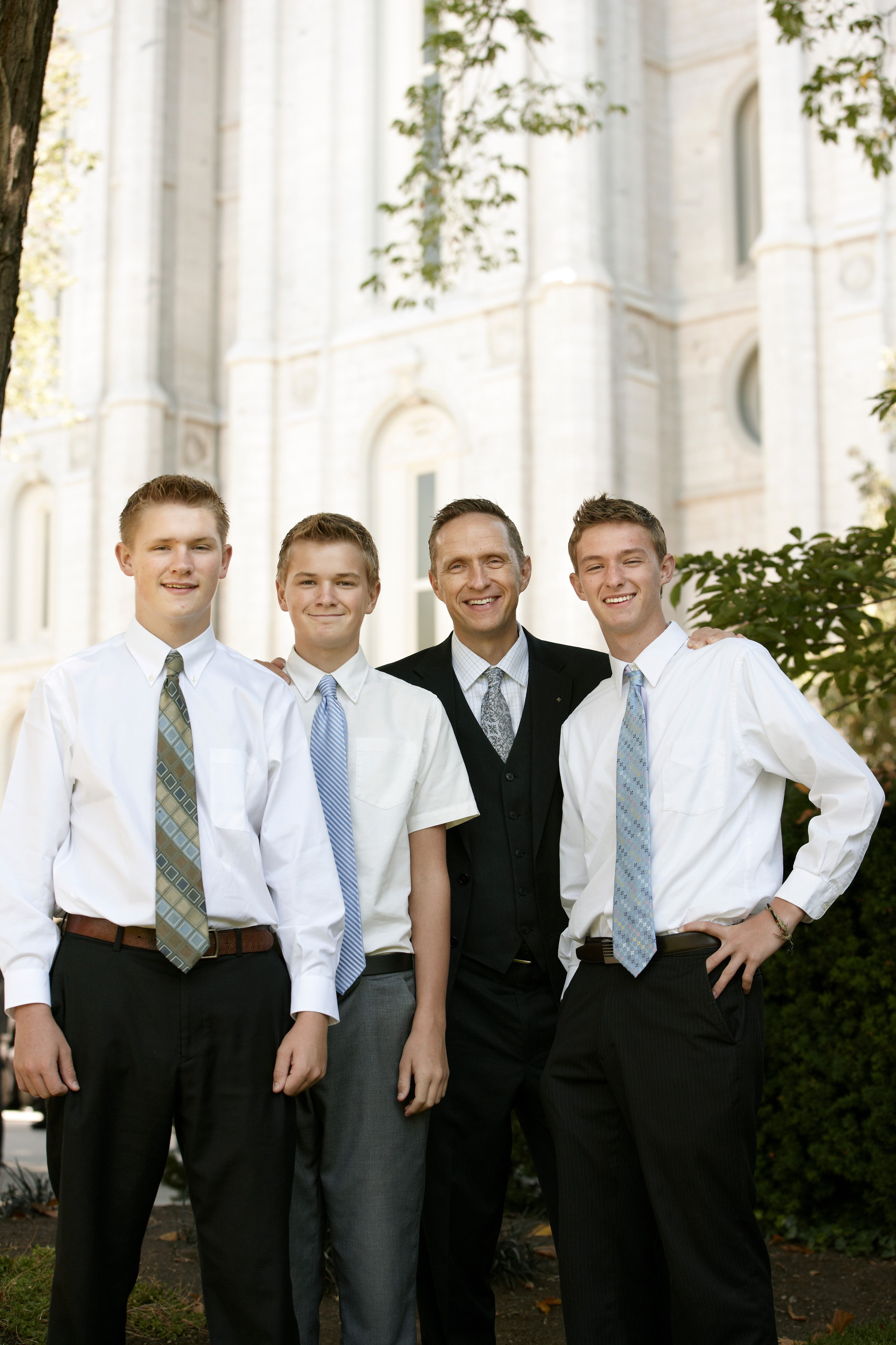 A man and three young men standing outside the temple, waiting for a session of general conference.