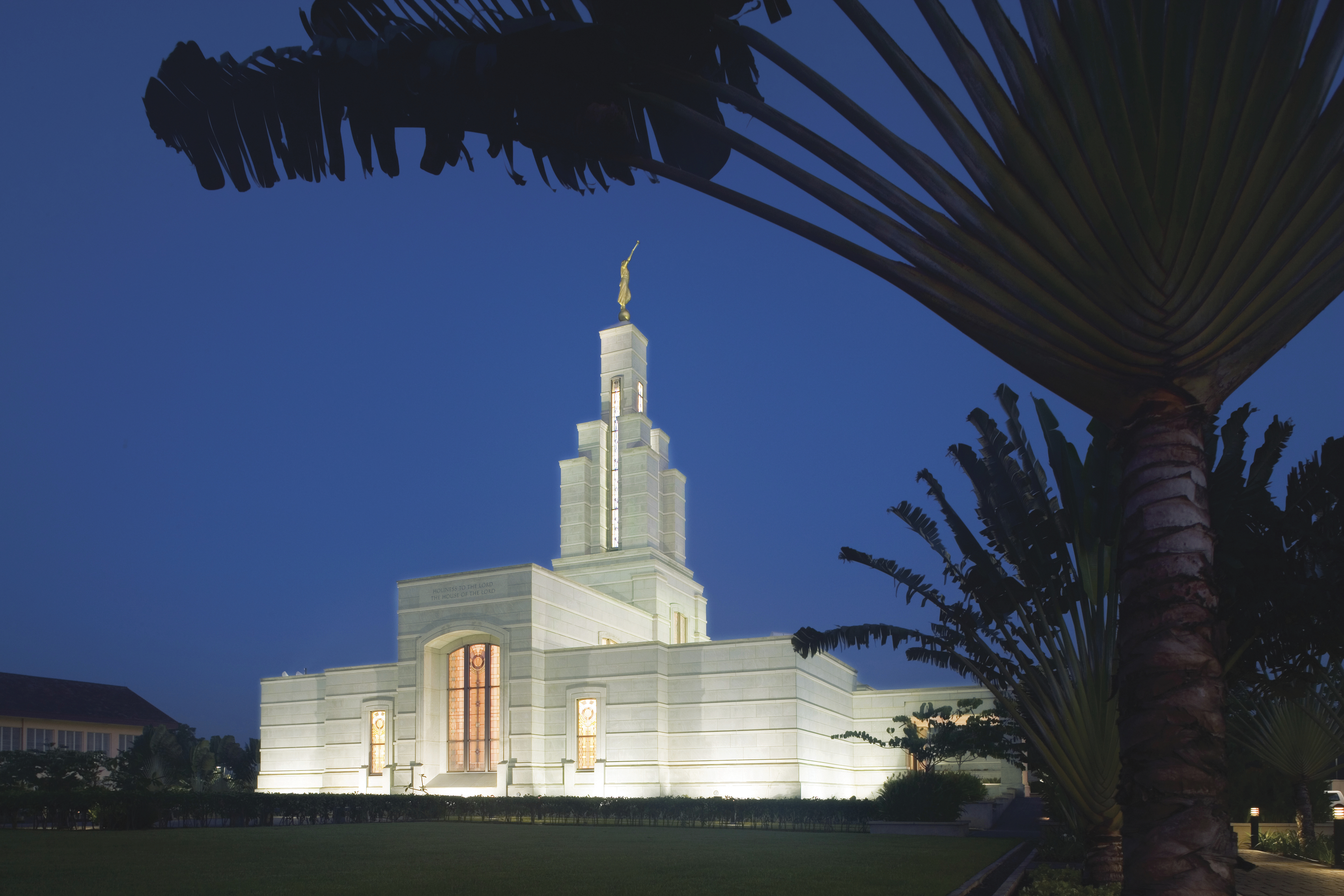 The Accra Ghana Temple is lit up at night.