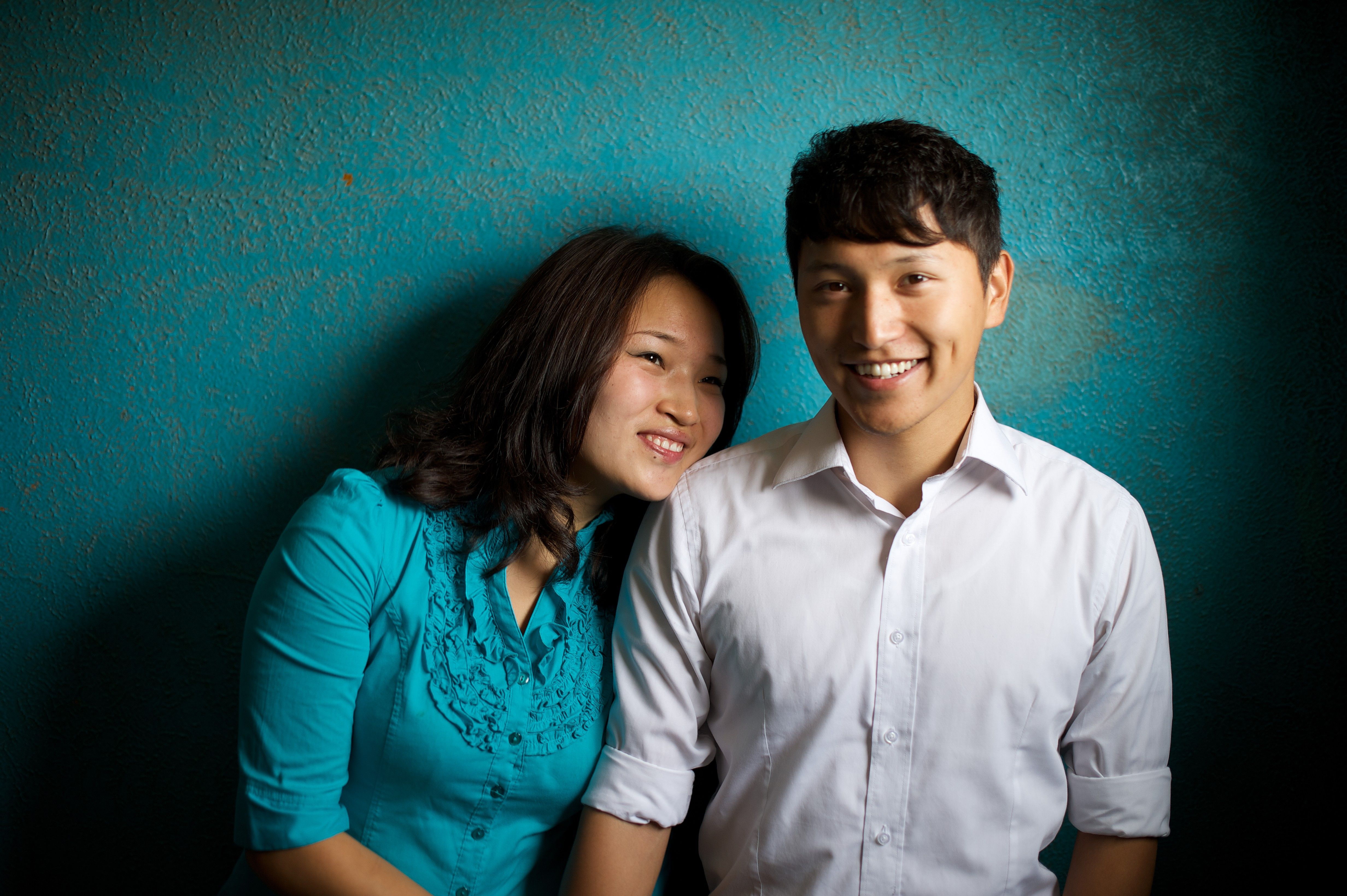 A portrait of a young couple from Mongolia, with a blue background.