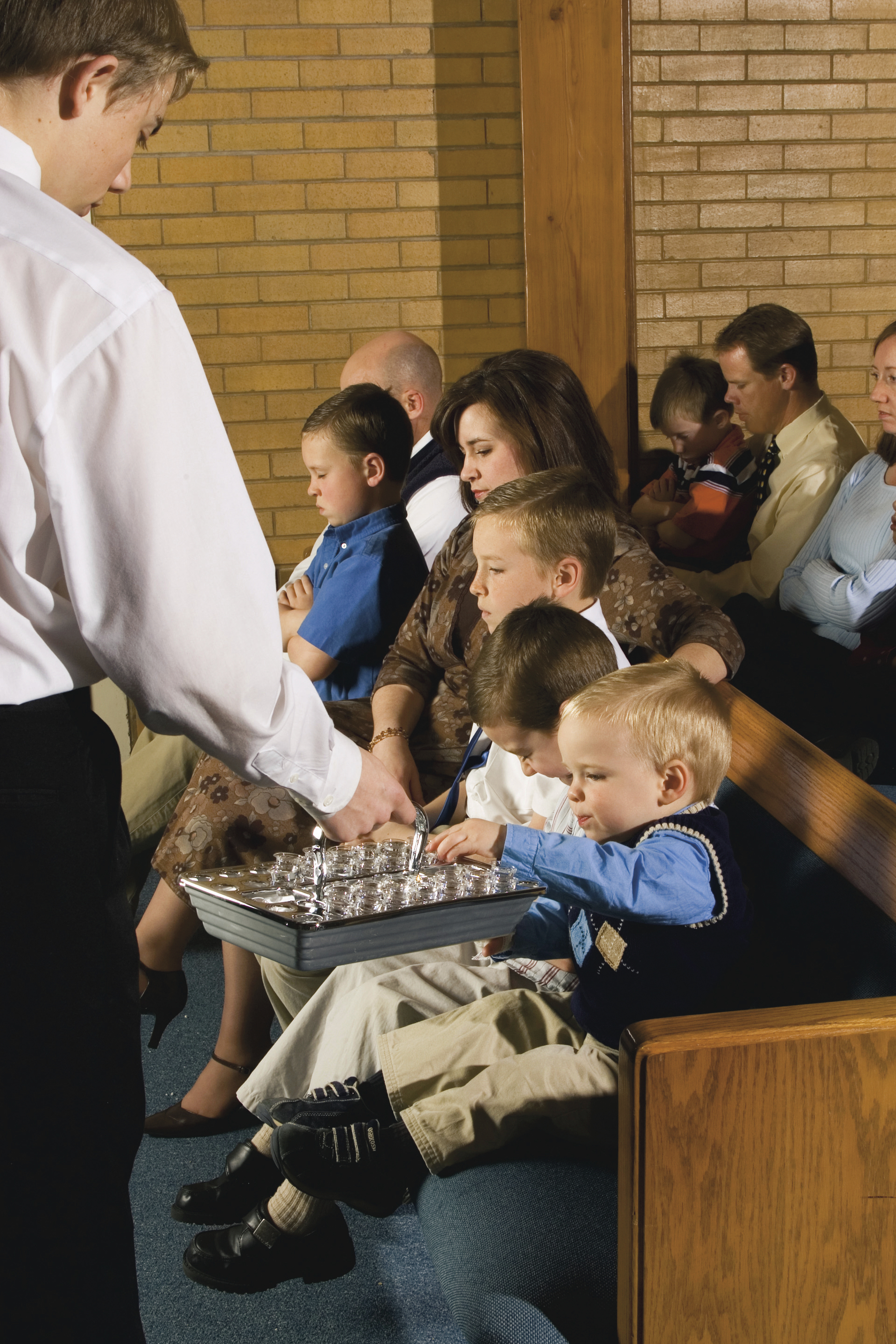 A young child reaches out to take a sacrament cup.