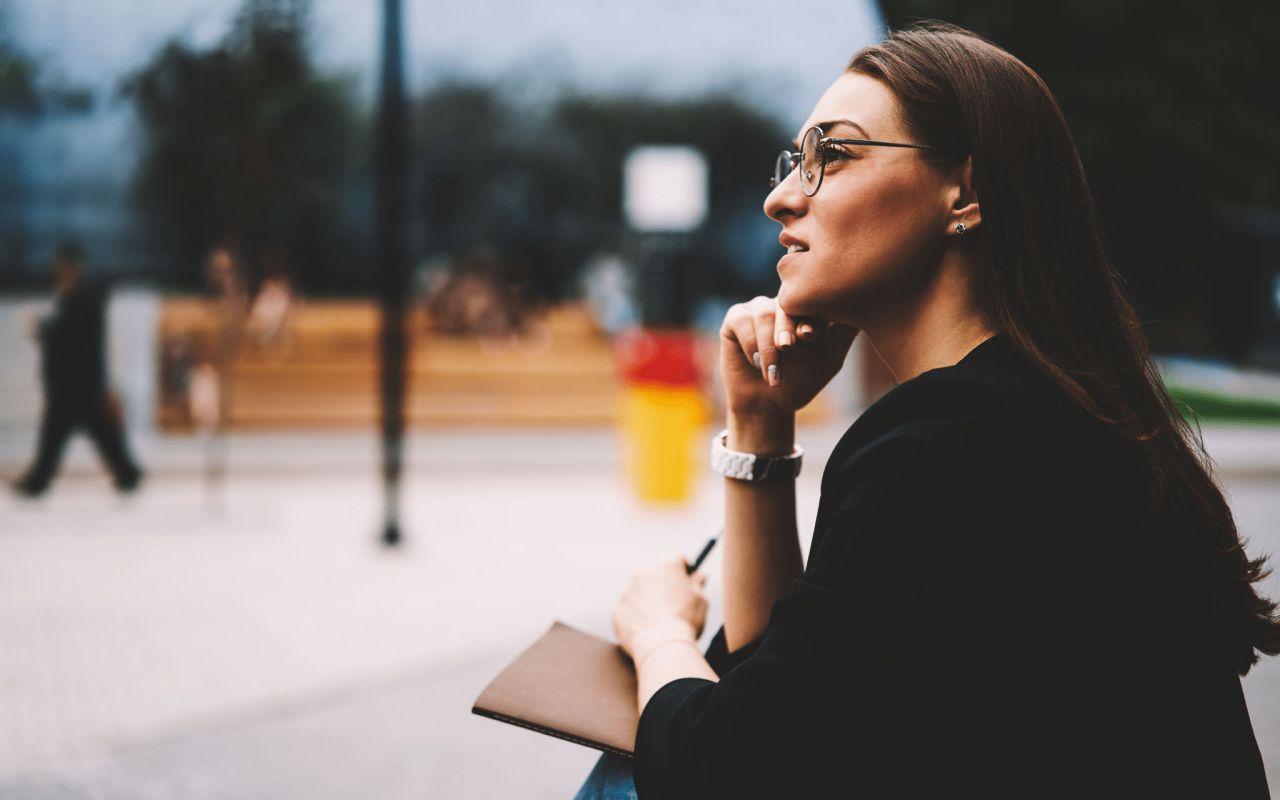 Una mujer sentada en un parque medita sobre el amor de Dios