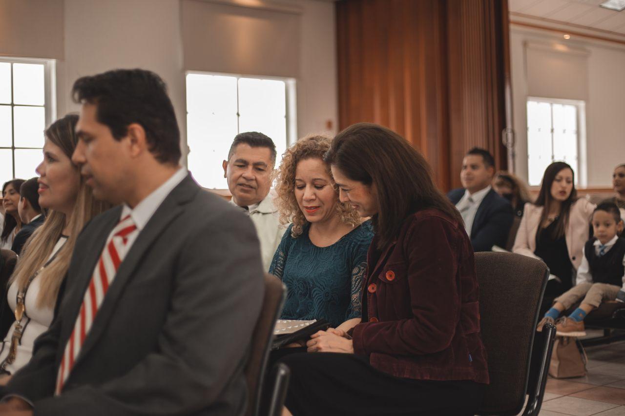 Personas participando en la reunión sacramental