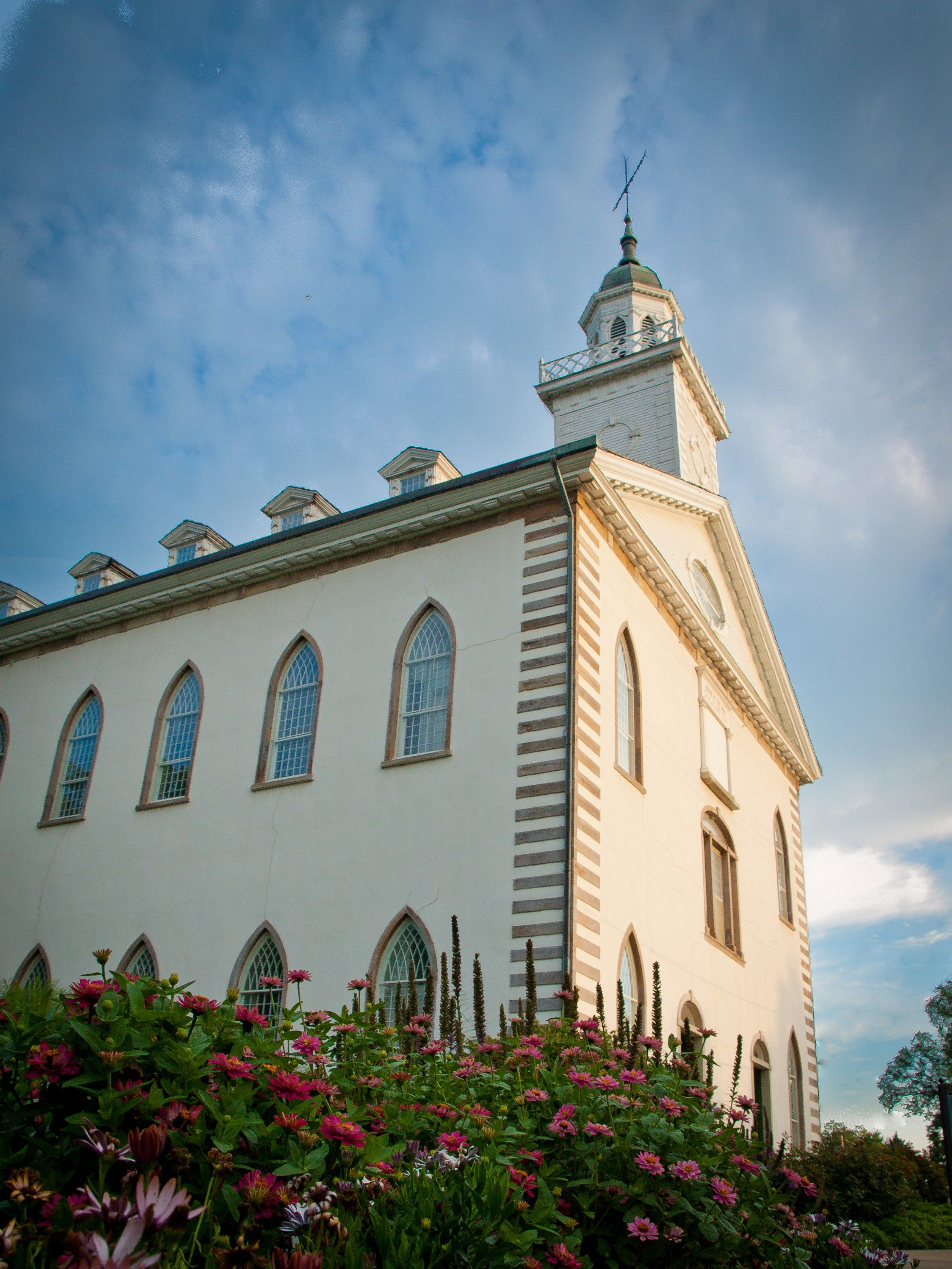 A side view of the Kirtland Temple in sunshine, including scenery.
