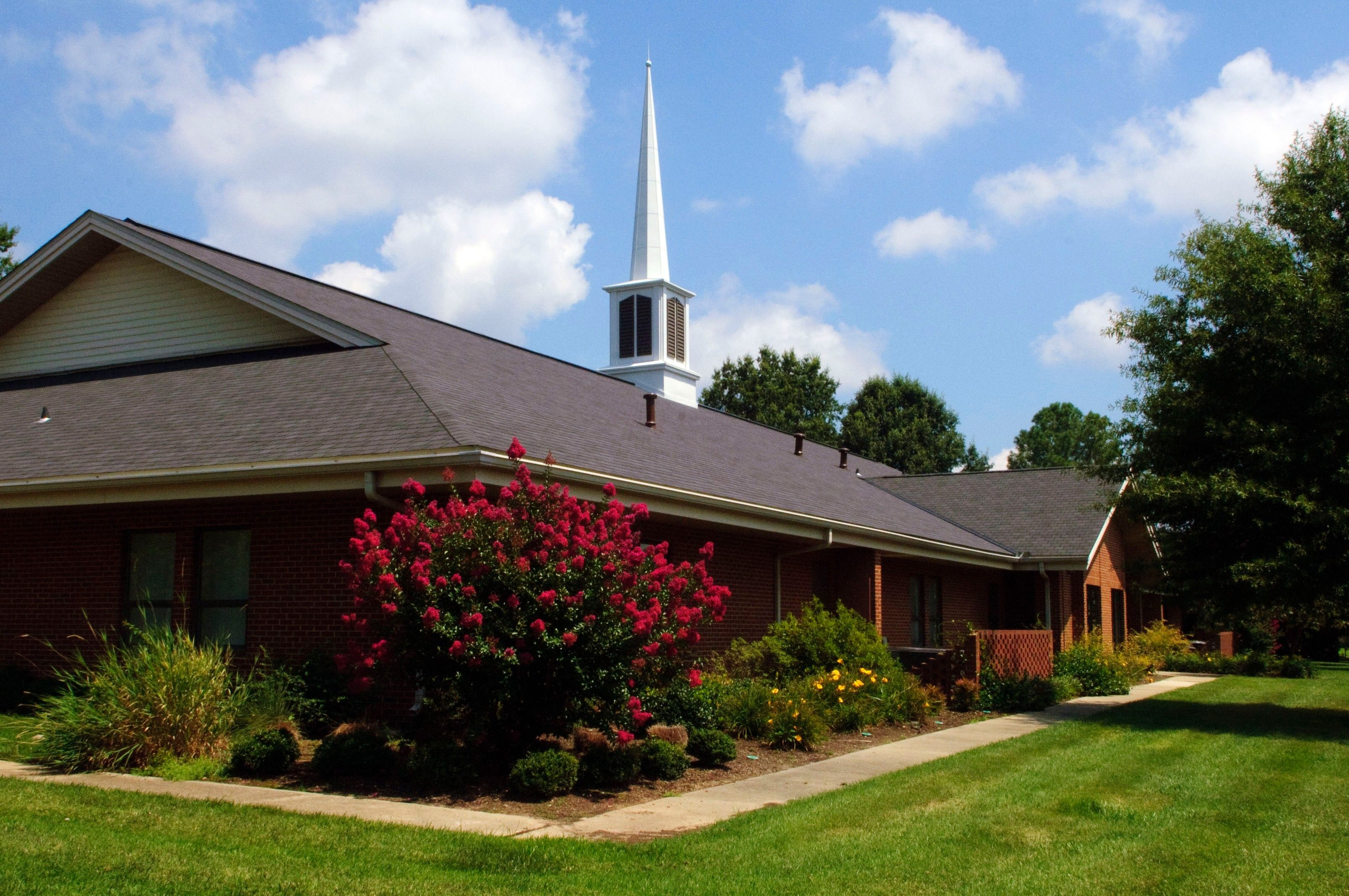 A side angle of a meetinghouse with a steeple surrounded by a grass lawn.