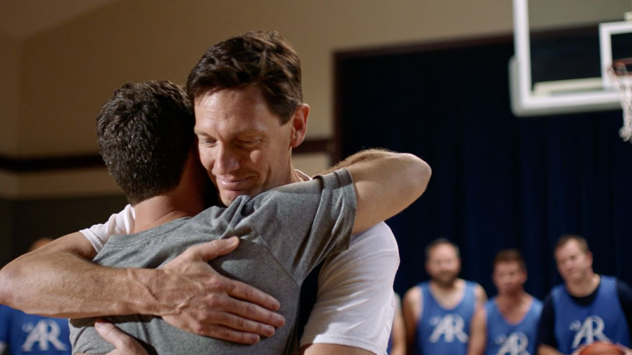 Two men hug on the basketball court