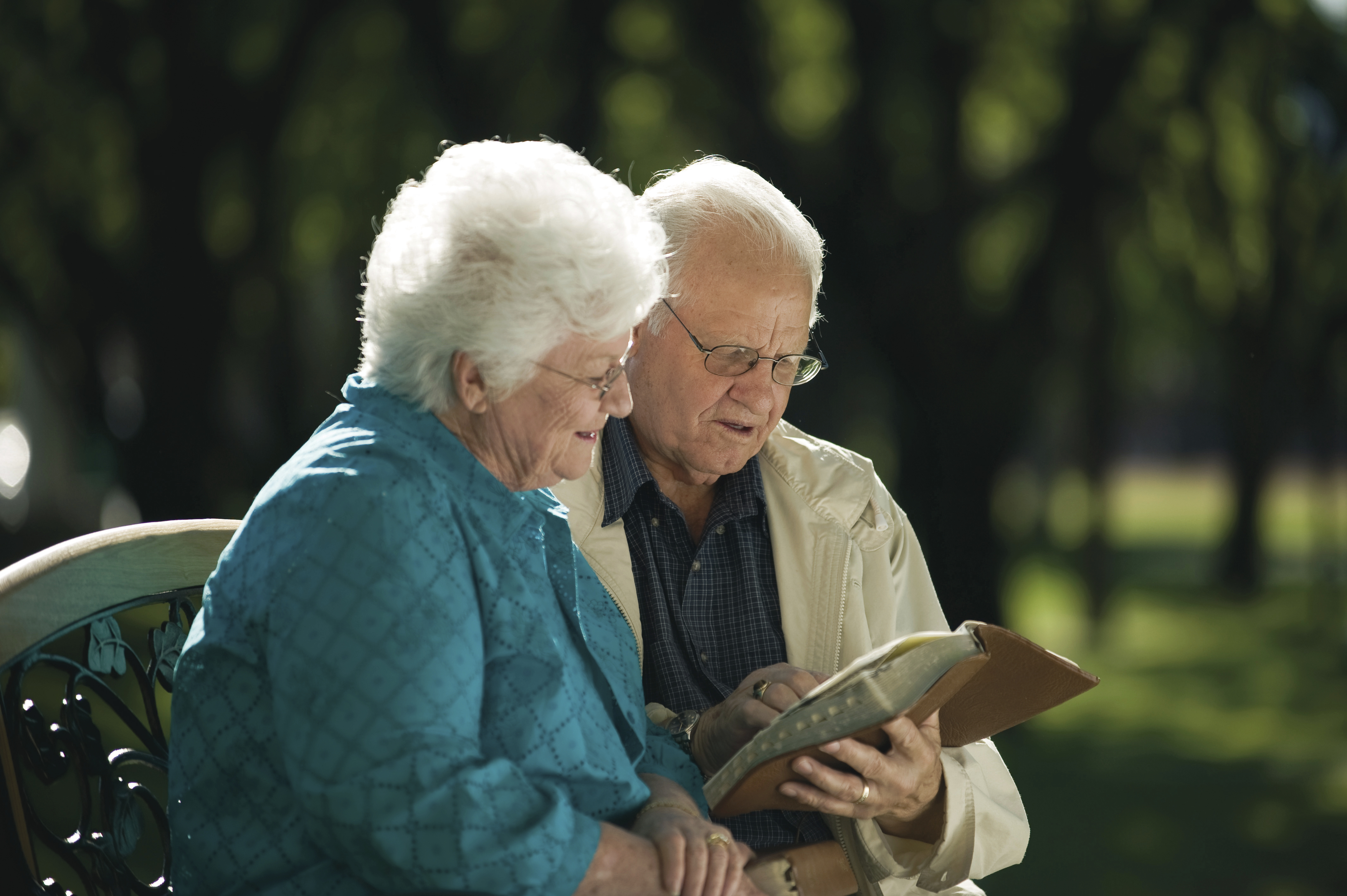 An elderly couple studies the scriptures together.