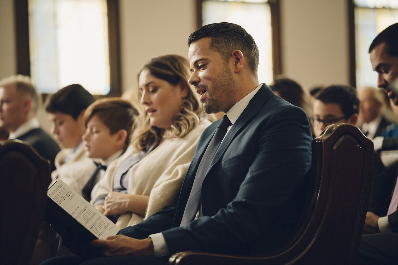 A family sit together on a chapel pew singing hymns with the congregation
