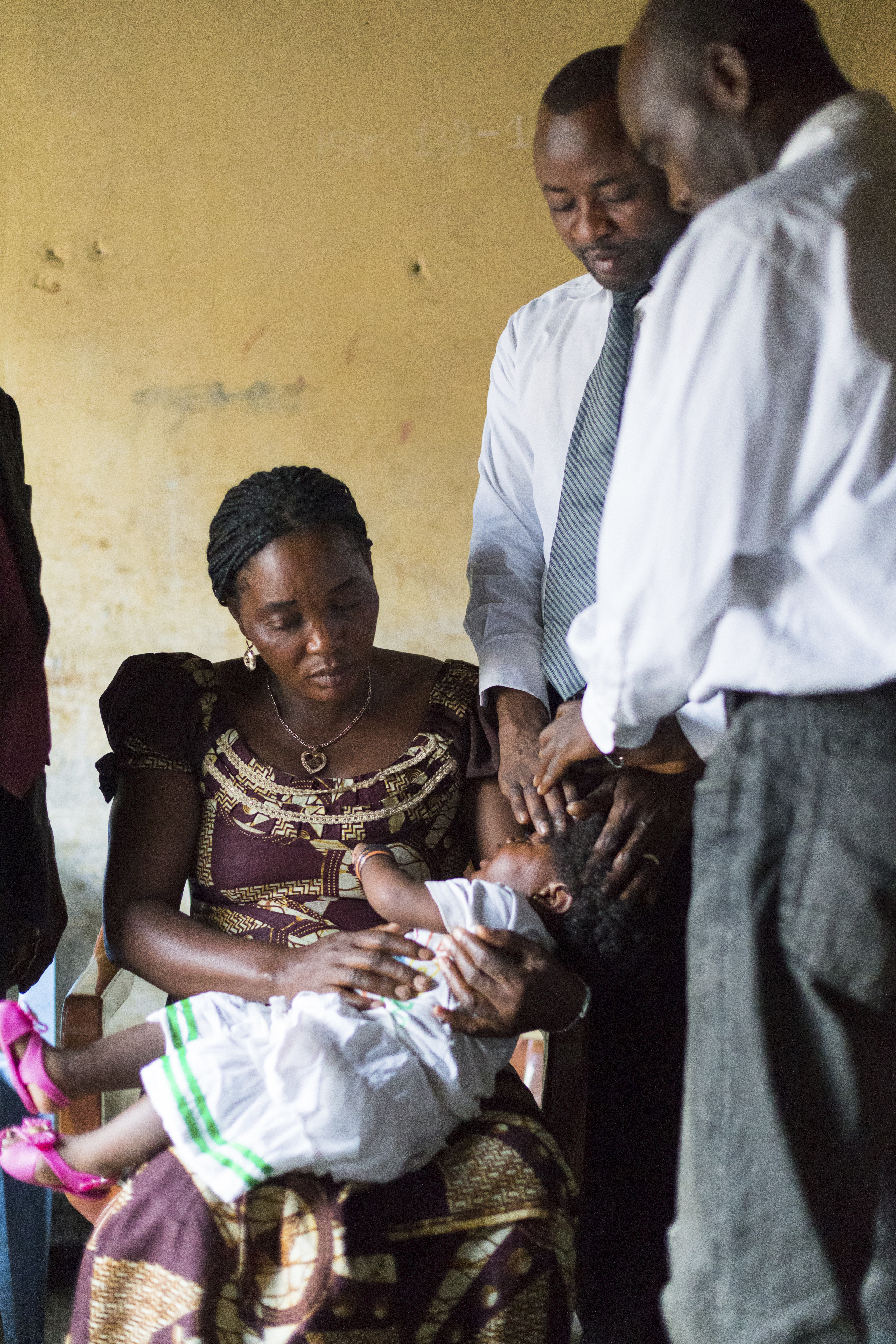 A woman in the Congo holding her baby, who is being blessed by two men.