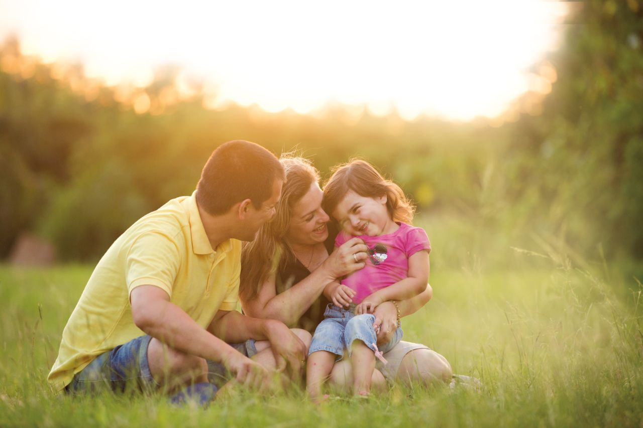 A young couple with their young daughter play together and enjoy family time