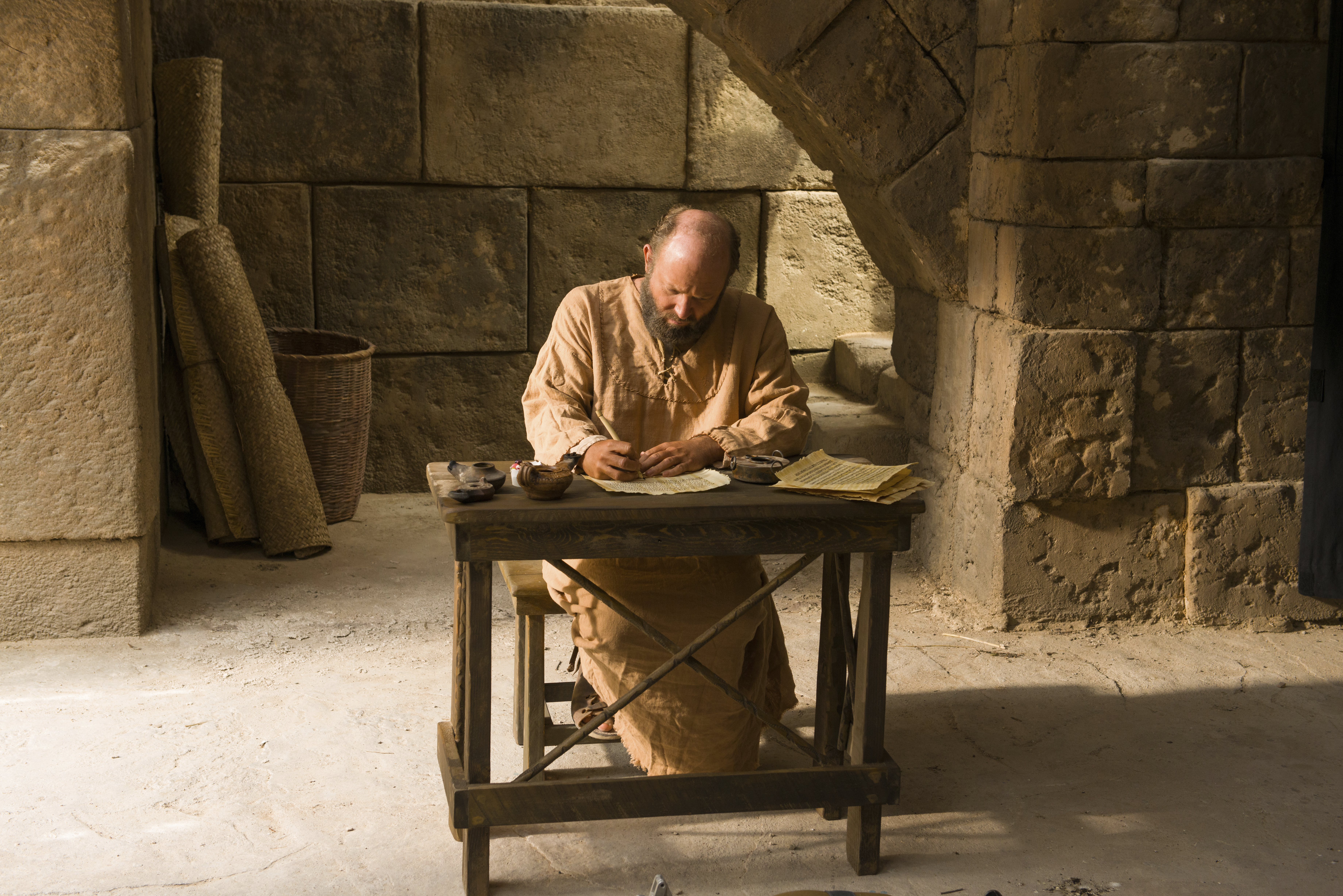 Paul sitting at a table and writing an epistle to the Corinthians.