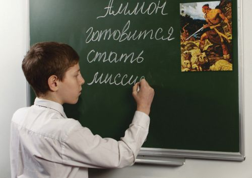boy writing words on chalkboard