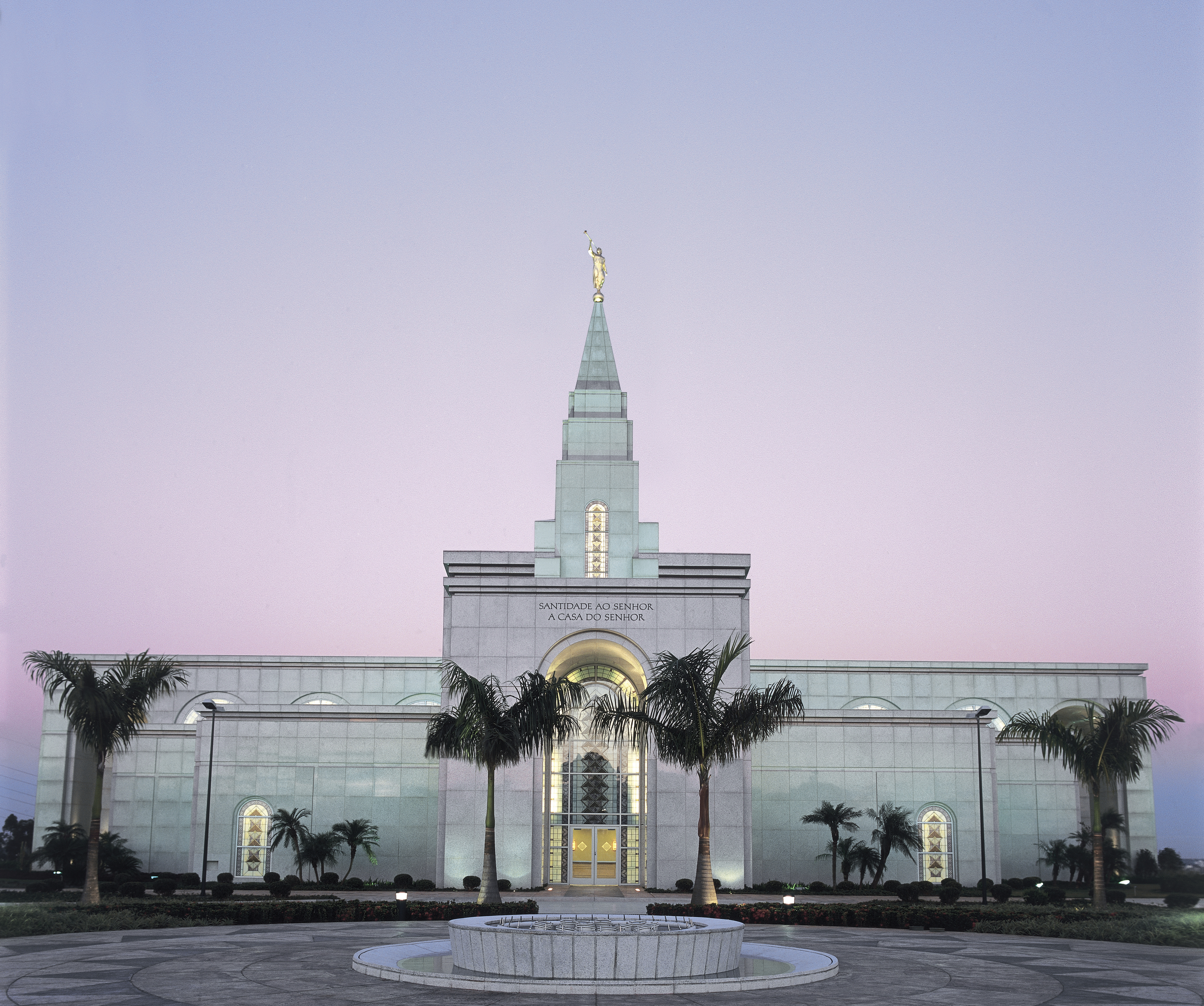 An exterior view of the Campinas Brazil Temple and its main entrance at dusk.