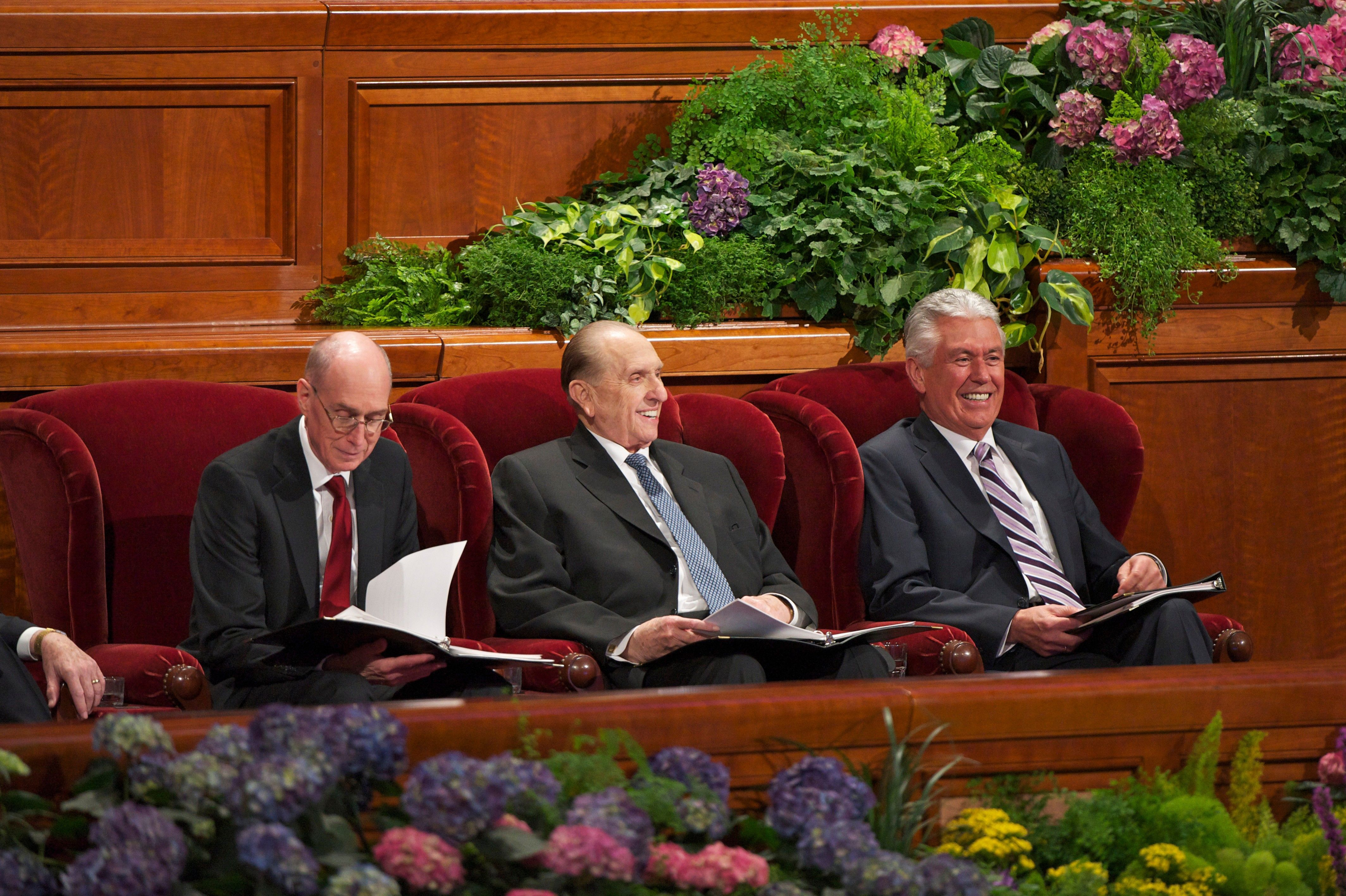 Thomas S. Monson, Dieter F. Uchtdorf, and Henry B. Eyring smiling and sitting in armchairs during general conference.