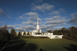 The Atlanta Georgia Temple in the daytime, with a green lawn in the foreground and small gray clouds overhead.