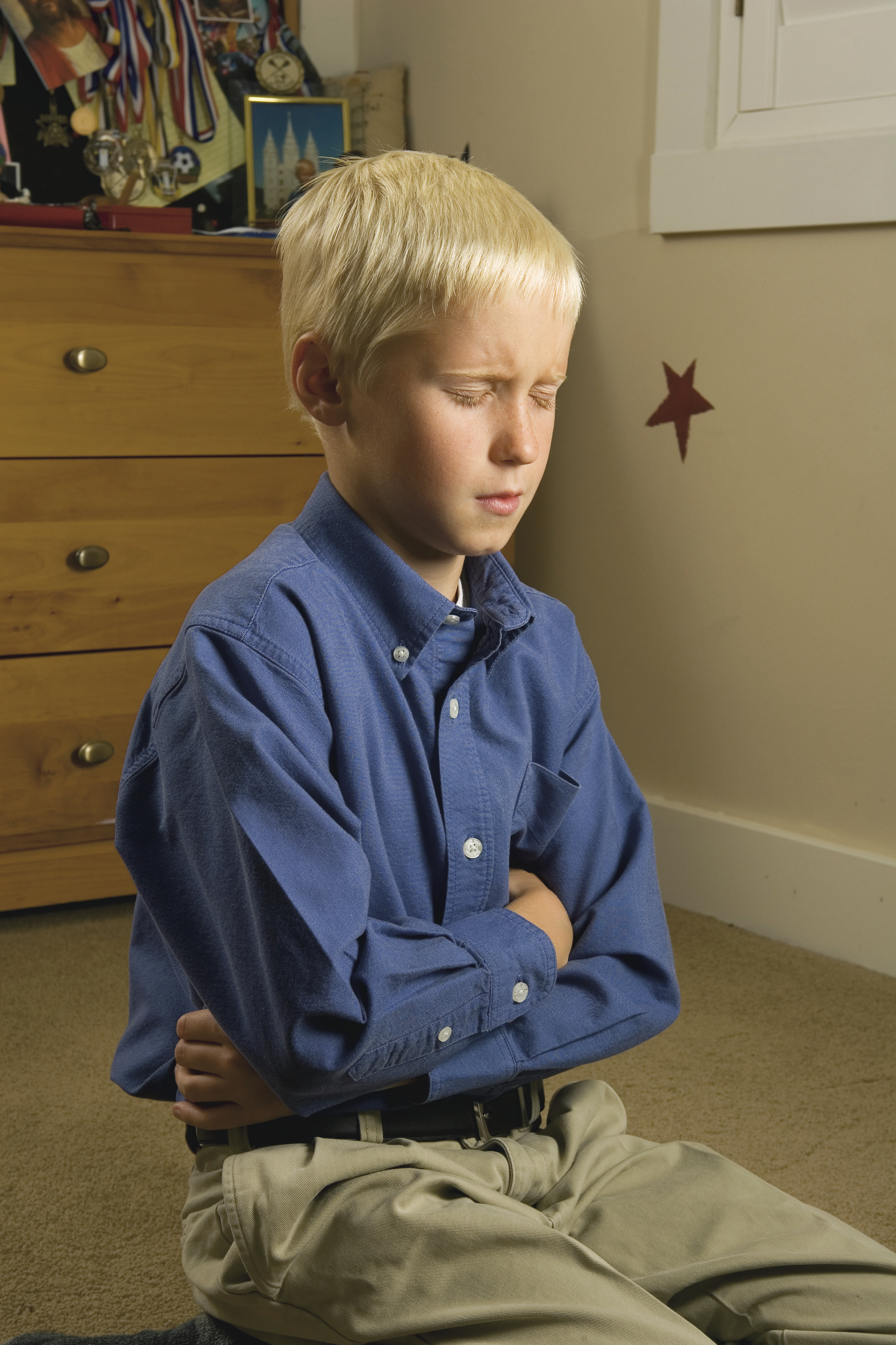 A young boy kneels to pray.