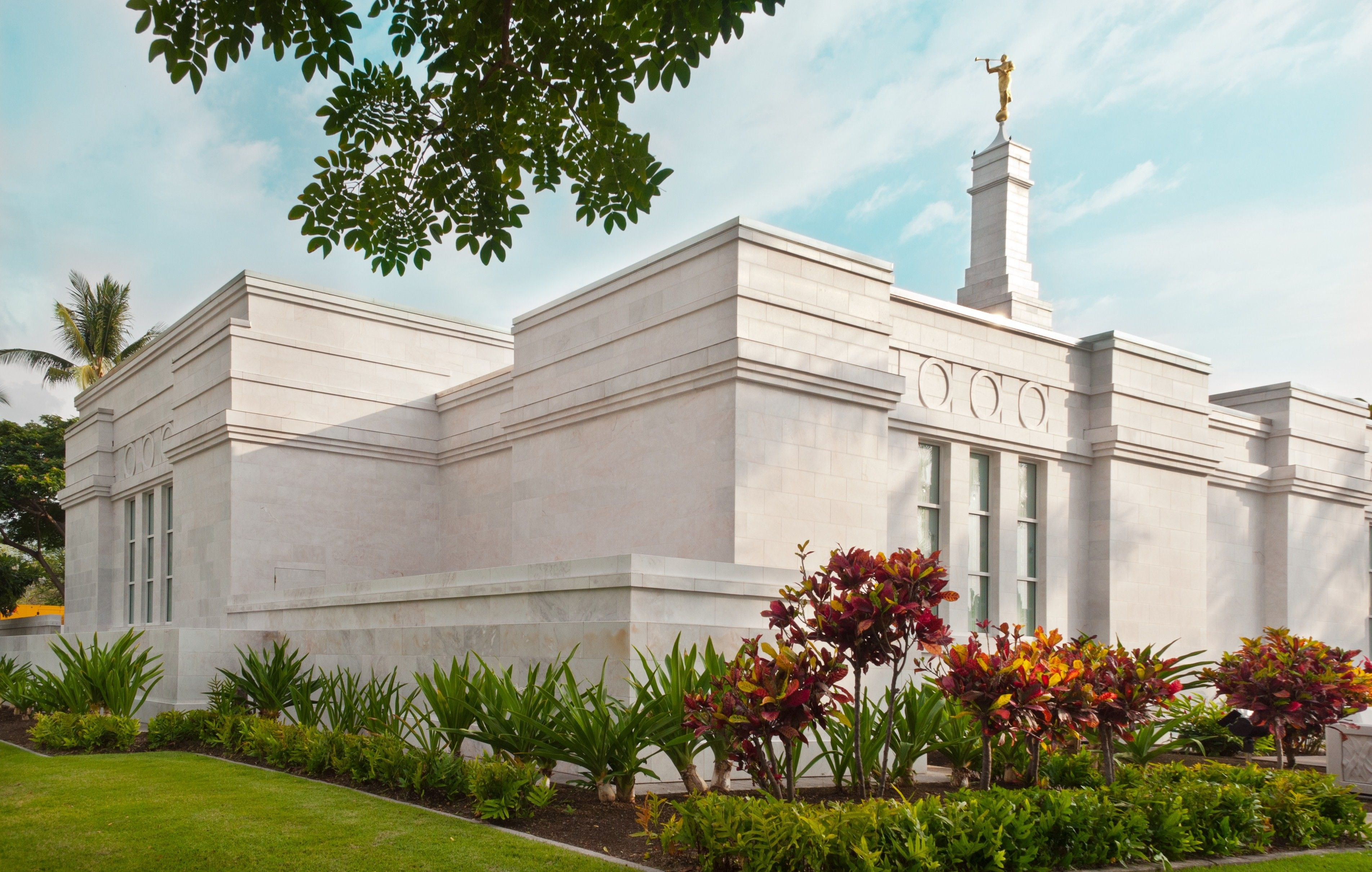 A side view of the Kona Hawaii Temple, including scenery and the exterior of the temple.