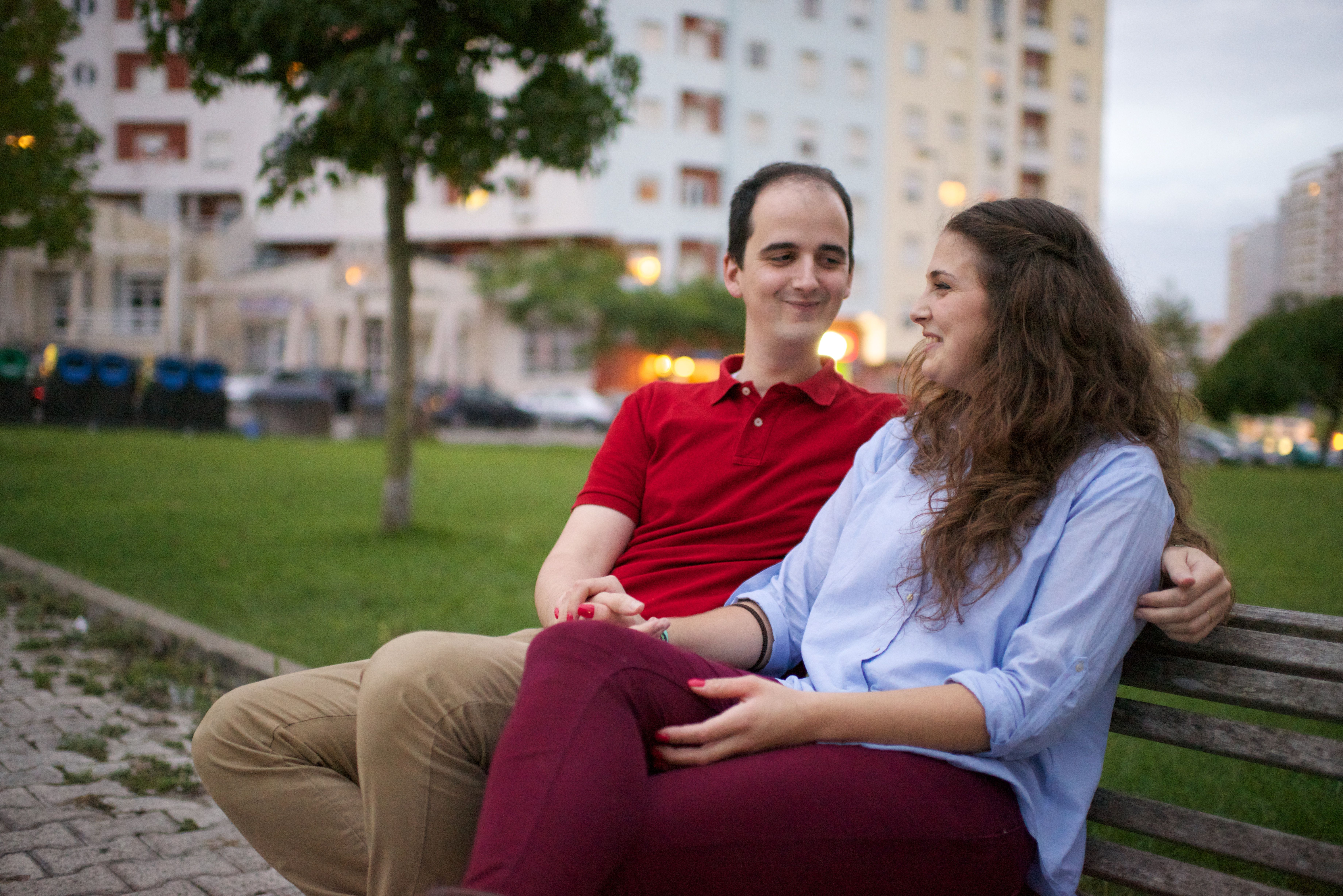 A young couple from Portugal sitting on a wooden bench outside.
