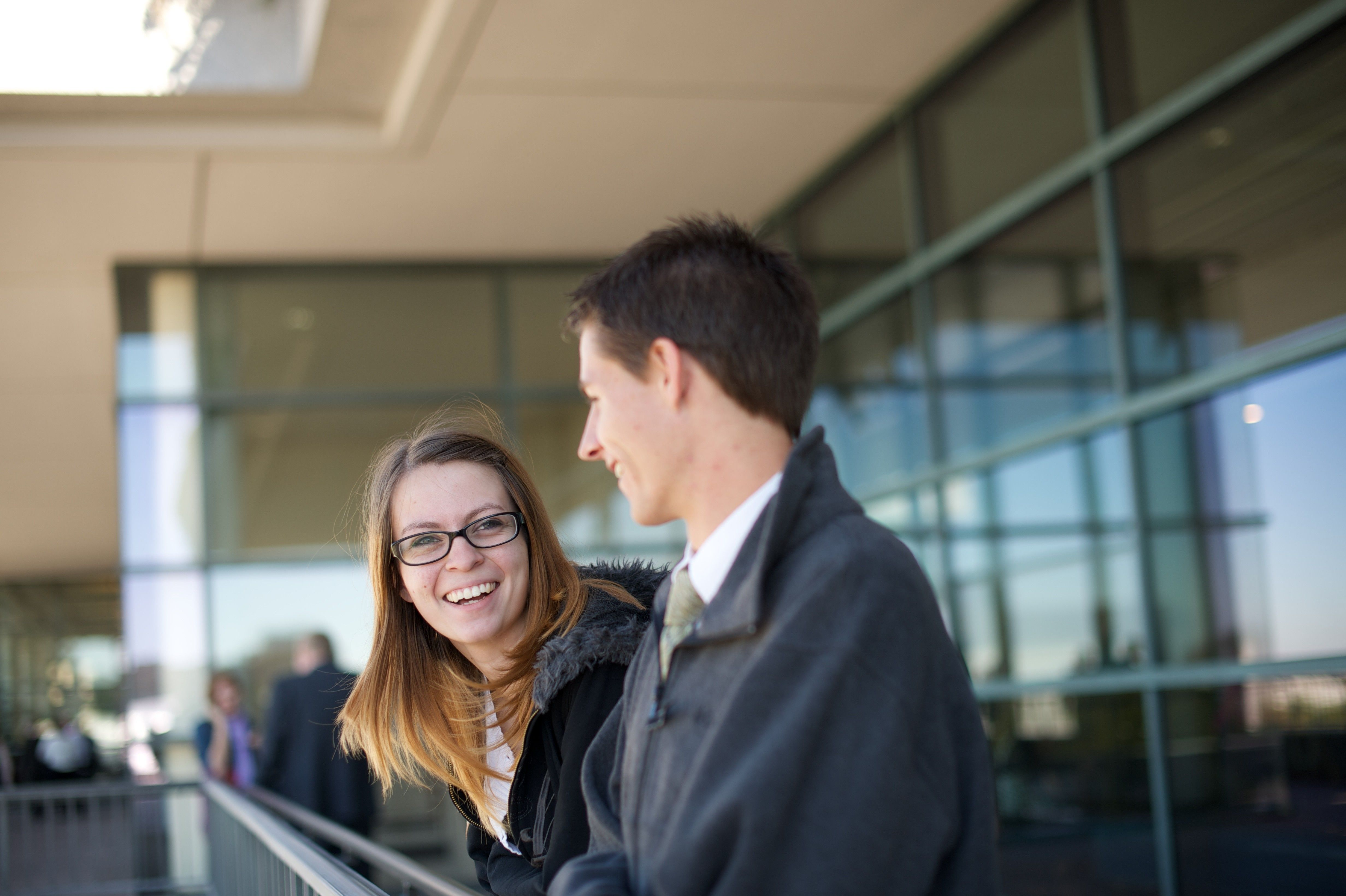 A man and woman smiling while standing outside the Conference Center.