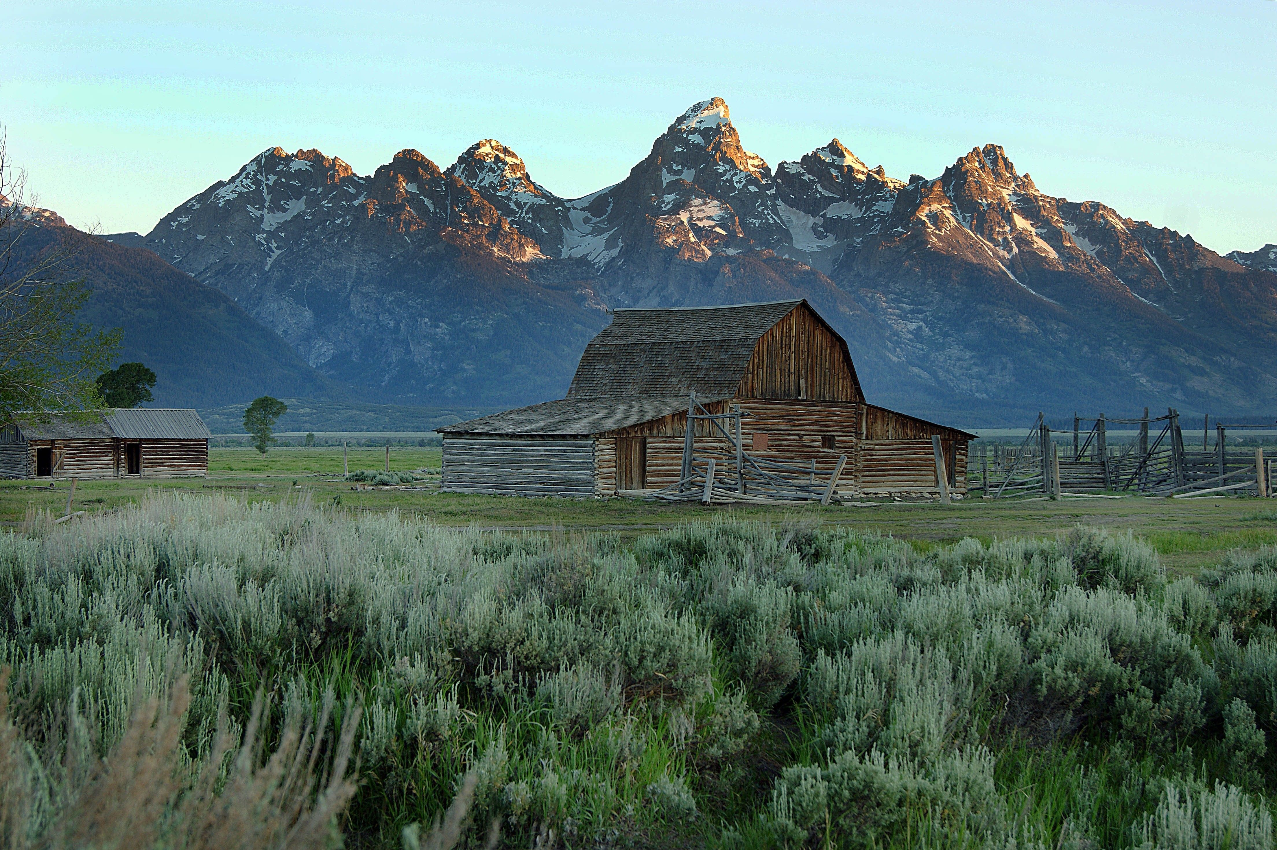 A barn with the Teton Mountains behind it.