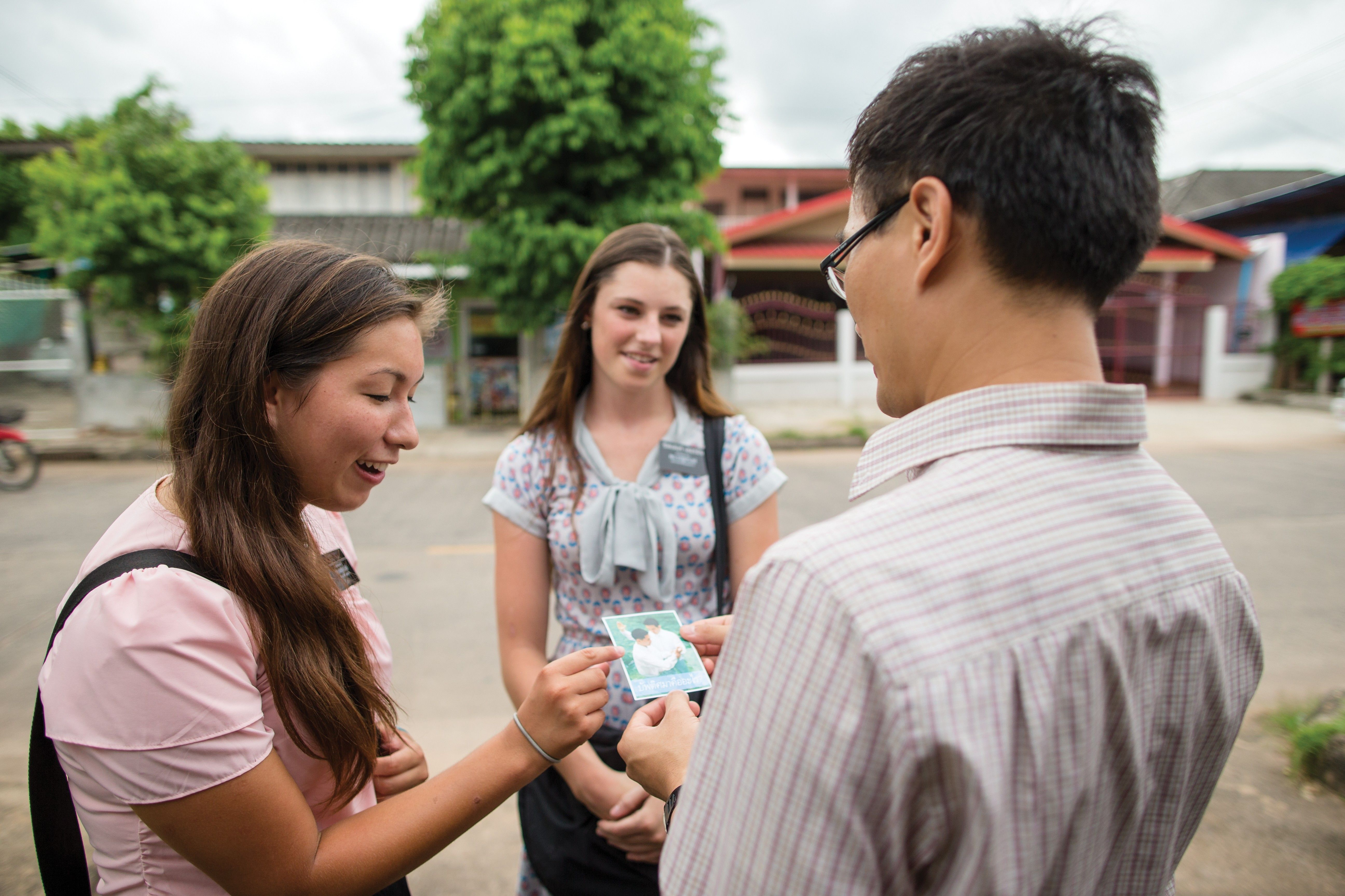 Sister missionaries handing a pass-along card to someone in Thailand.