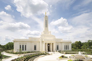 A front view of the Indianapolis Indiana Temple on a sunny day with clouds overhead.