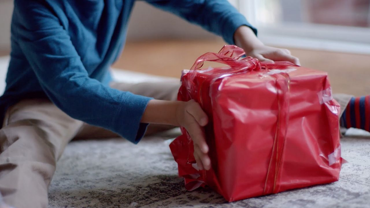 A young boy wraps a Christmas gift