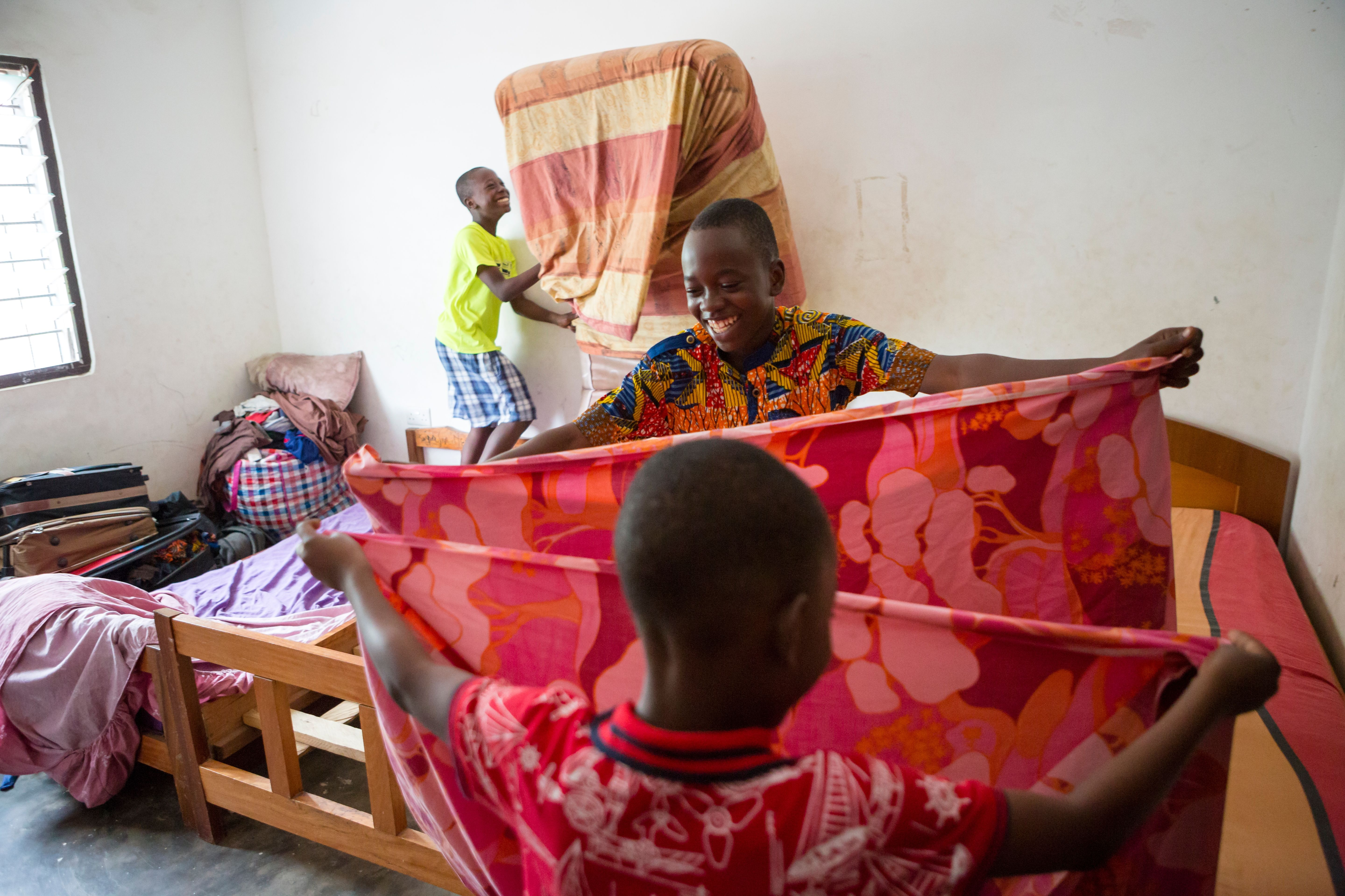 Three brothers in Ghana wearing bright clothing, helping each other with family chores by making beds and folding bedding.