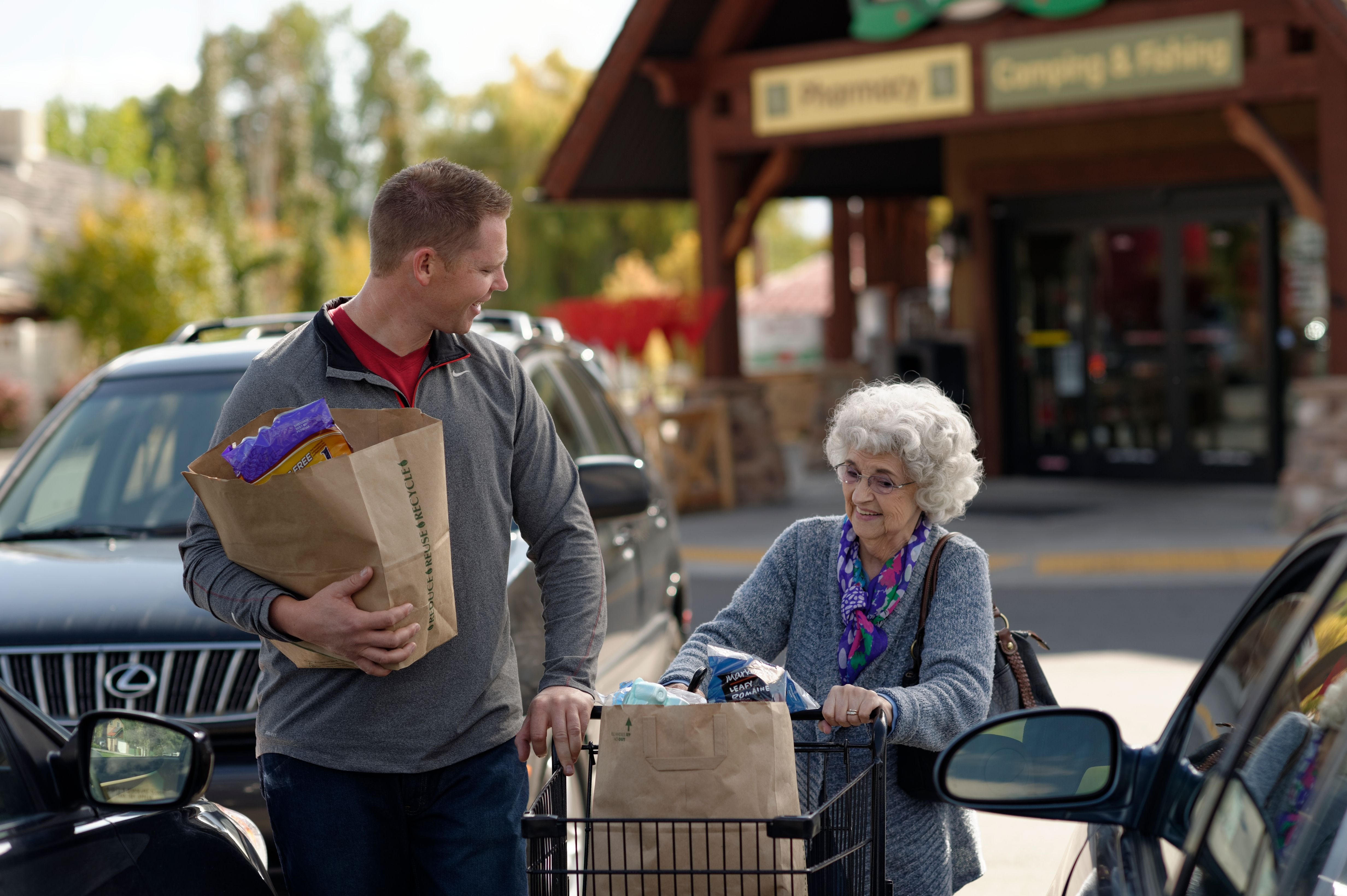 A young man helps an elderly woman carry groceries out to her car.
