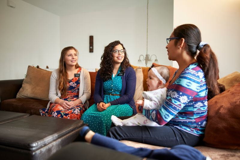Two sister missionaries teach a young mother and her son in her living room